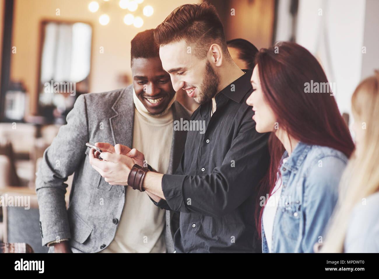 Portrait von fröhlichen jungen Freunden bei smart phone, während im Cafe sitzen. Gemischte Rasse Menschen in Restaurant mit Handy Stockbild