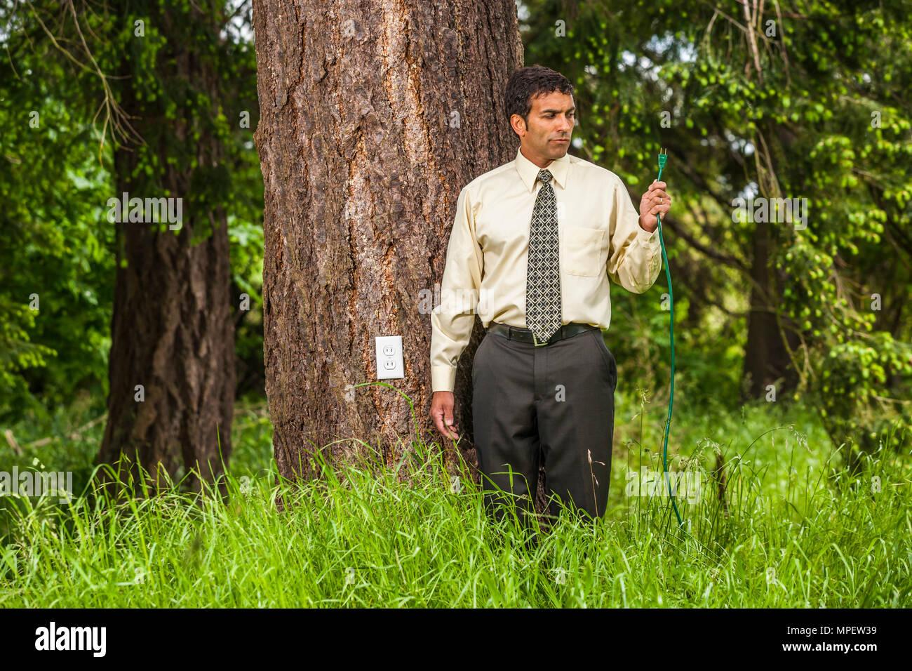 Konzeptionelle geschossen von einem Geschäftsmann mit einem grünen Kabel mit einer Steckdose im Baum neben ihm. Zur Veranschaulichung von Green Power. Stockbild