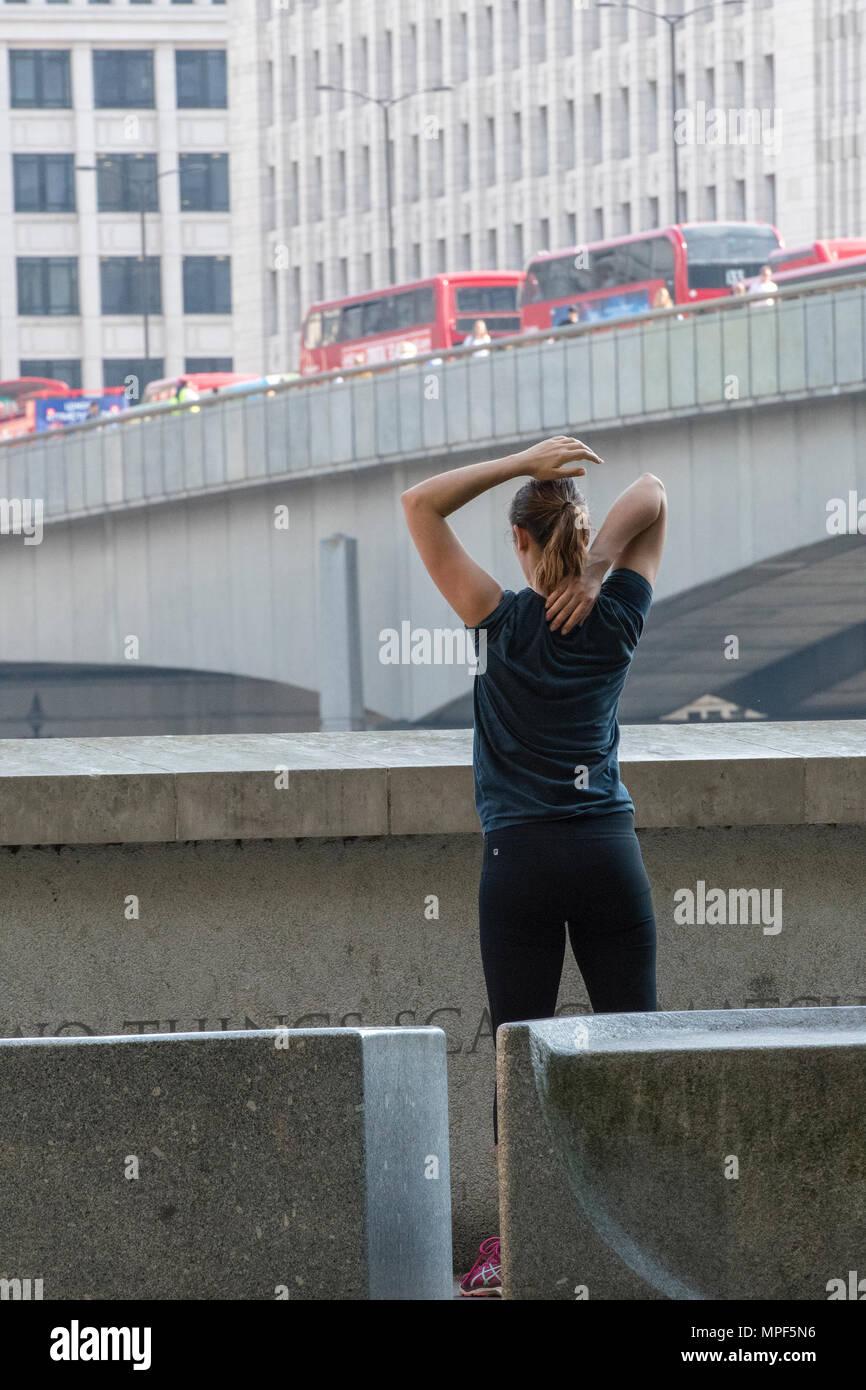 Eine junge Frau, die Ausübung oder Wahrnehmung während der morgendlichen Rush hour in Central London. Stretching Übungen die Muskulatur zu lockern nach der Ausführung. Stockbild