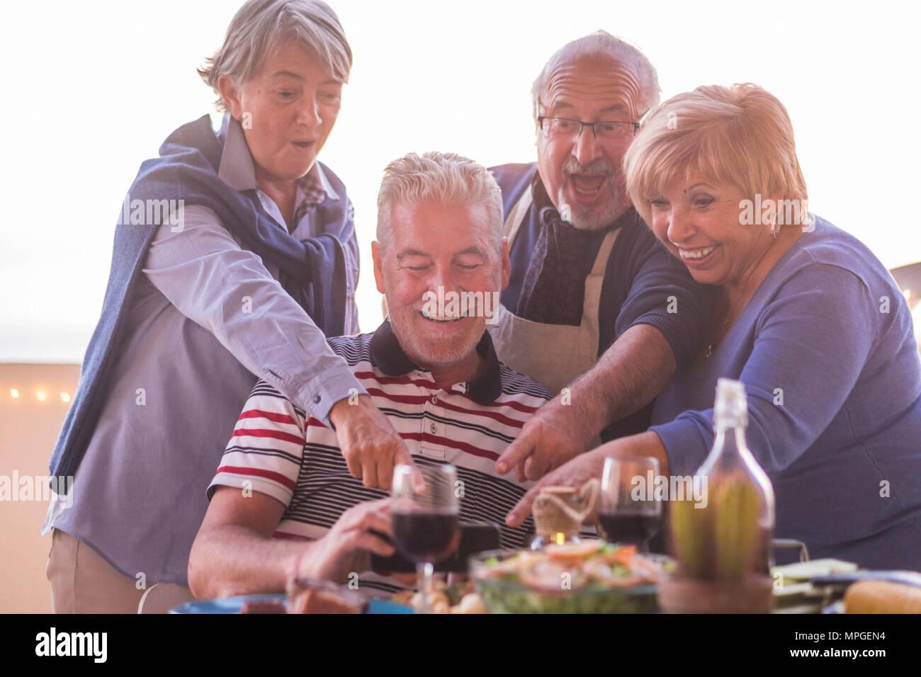 Zwei schöne Paare tun Bild mit Mobiltelefon, während das Abendessen auf der Dachterrasse im Freien im Urlaub. Lifestyle für Pensionierte glücklich Konzept Stockbild