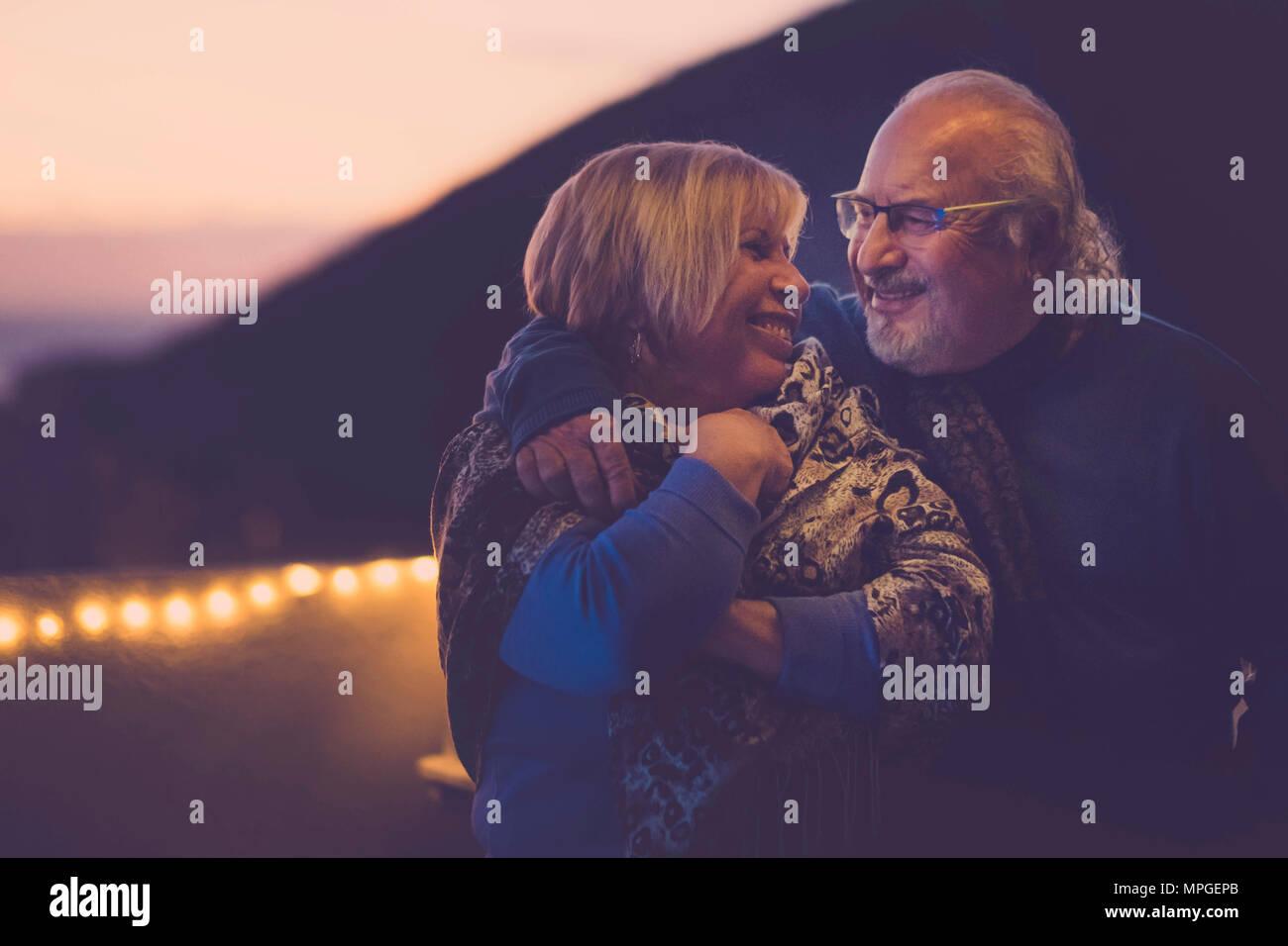 Mann und Frau senior Herren gealtert in Liebe umarmen und Spaß auf der Dachterrasse im Urlaub zu Hause Lächeln haben. Nacht Licht Atmosphäre für romantische Szene. t Stockbild