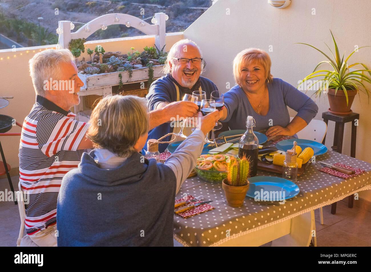 Nach Gruppe von Menschen, die gutes Abendessen im Freien auf der Terrasse. Die Freundschaft genießen mit Zeit zusammen trinken und feiern, Urlaub oder Ruhestand c Stockbild