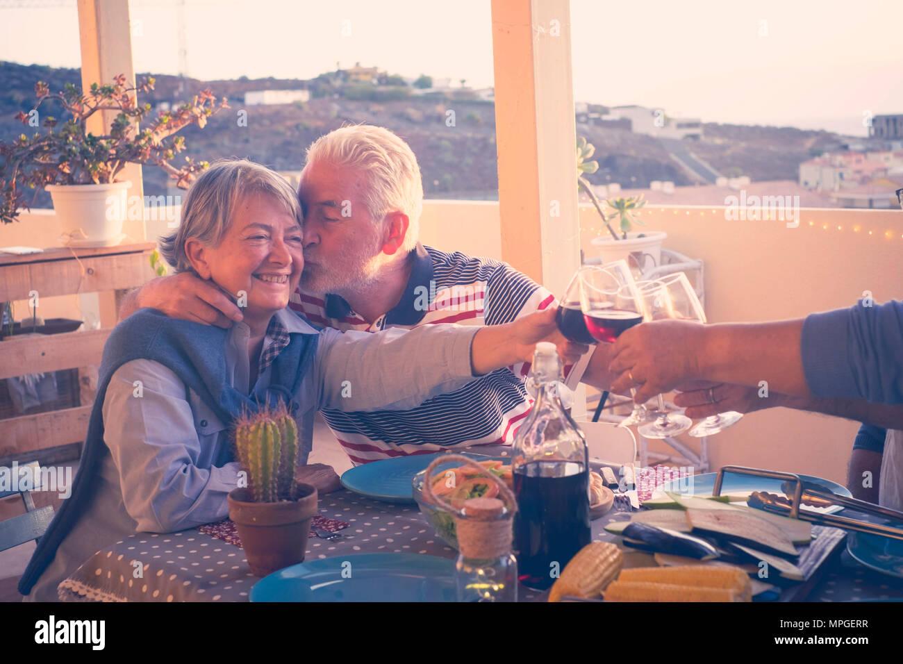 Gruppe von im Alter von älteren Freunde Erwachsene essen und Party schöne Zeit in der Dachterrasse im Freien mit Wein und Essen. Spaß und Küssen du Stockbild