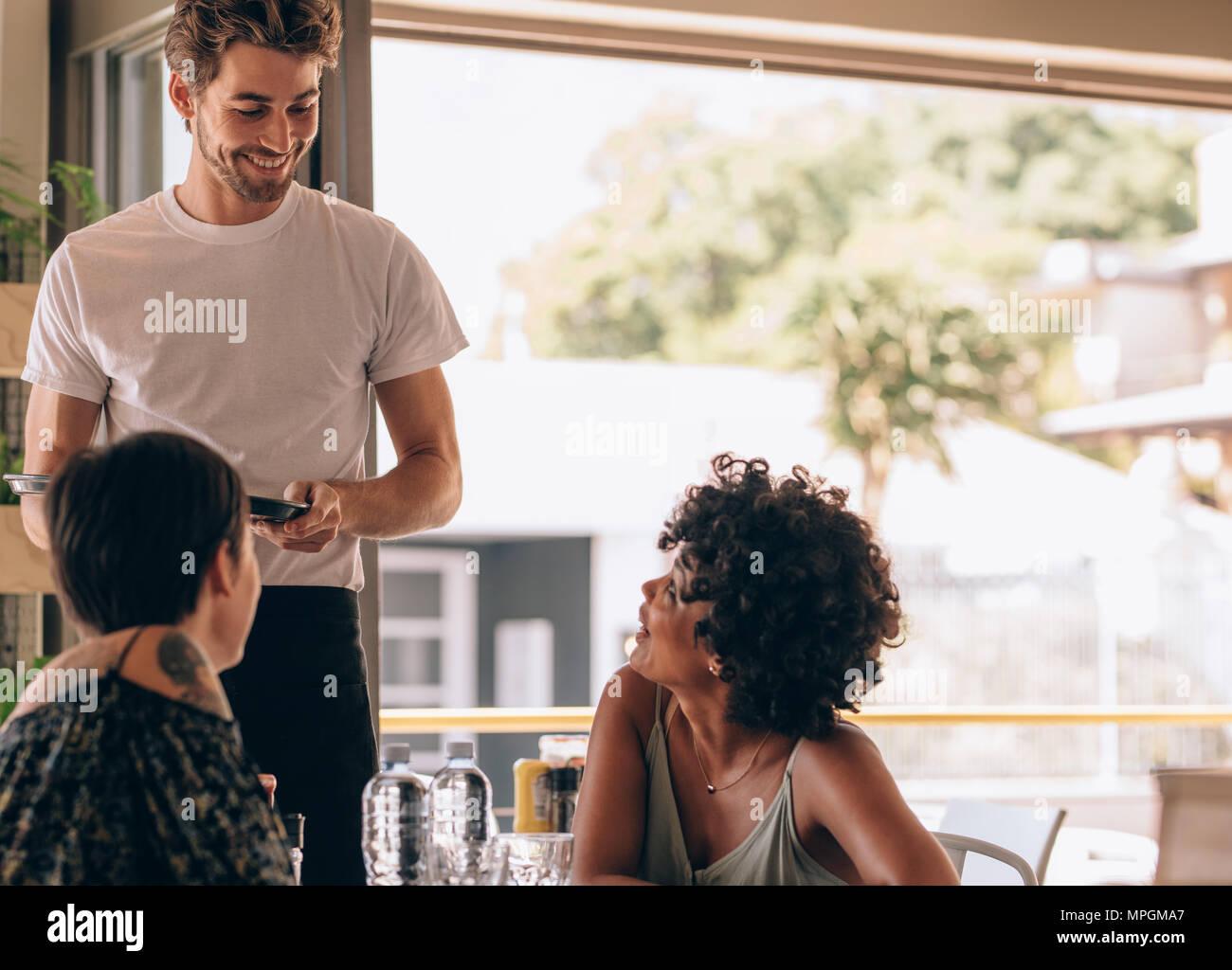 145cb1bc554877 Junge Frau mit einem Freund im Café zu bestellen Kellner. Zwei Frauen im  Cafe sitzen