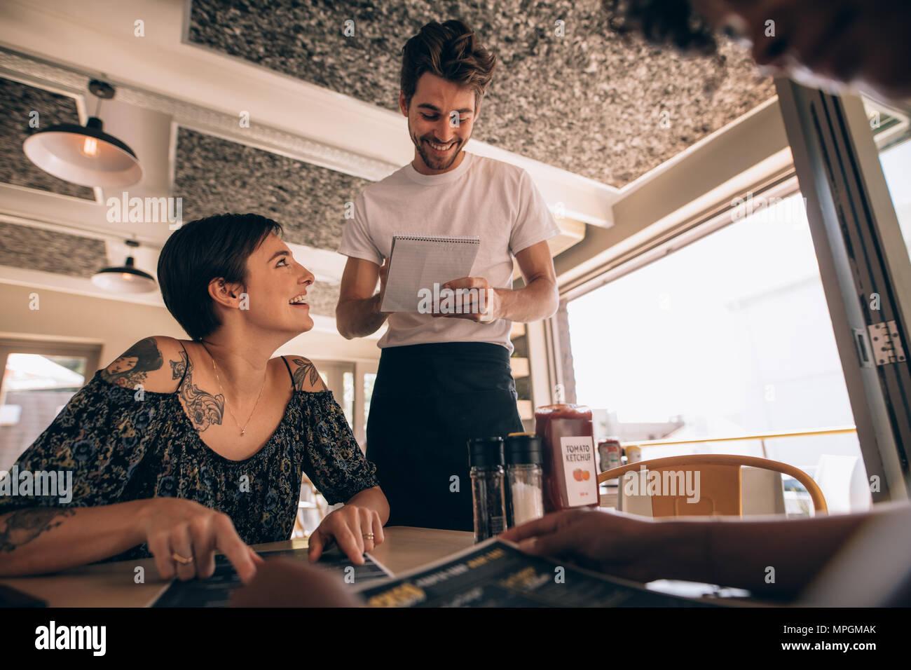 6160721b4fe126 Frau Kellner im Restaurant zu sprechen. Junge Frau im Cafe sitzen mit  Kellner die Bestellung.