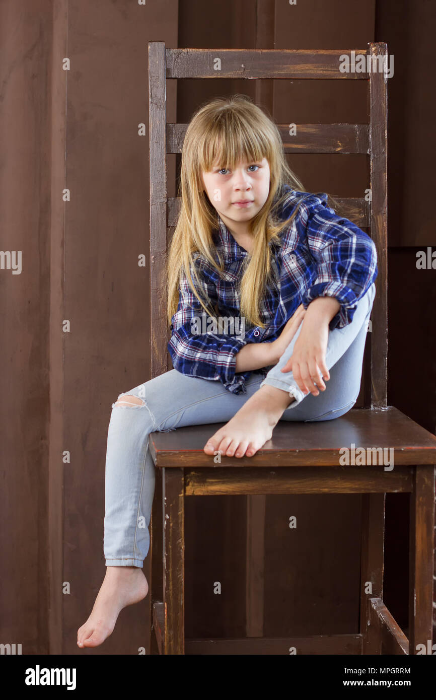 m dchen 6 jahre alt in jeans und ein blaues hemd sitzt auf einem hohen stuhl in einem zimmer. Black Bedroom Furniture Sets. Home Design Ideas