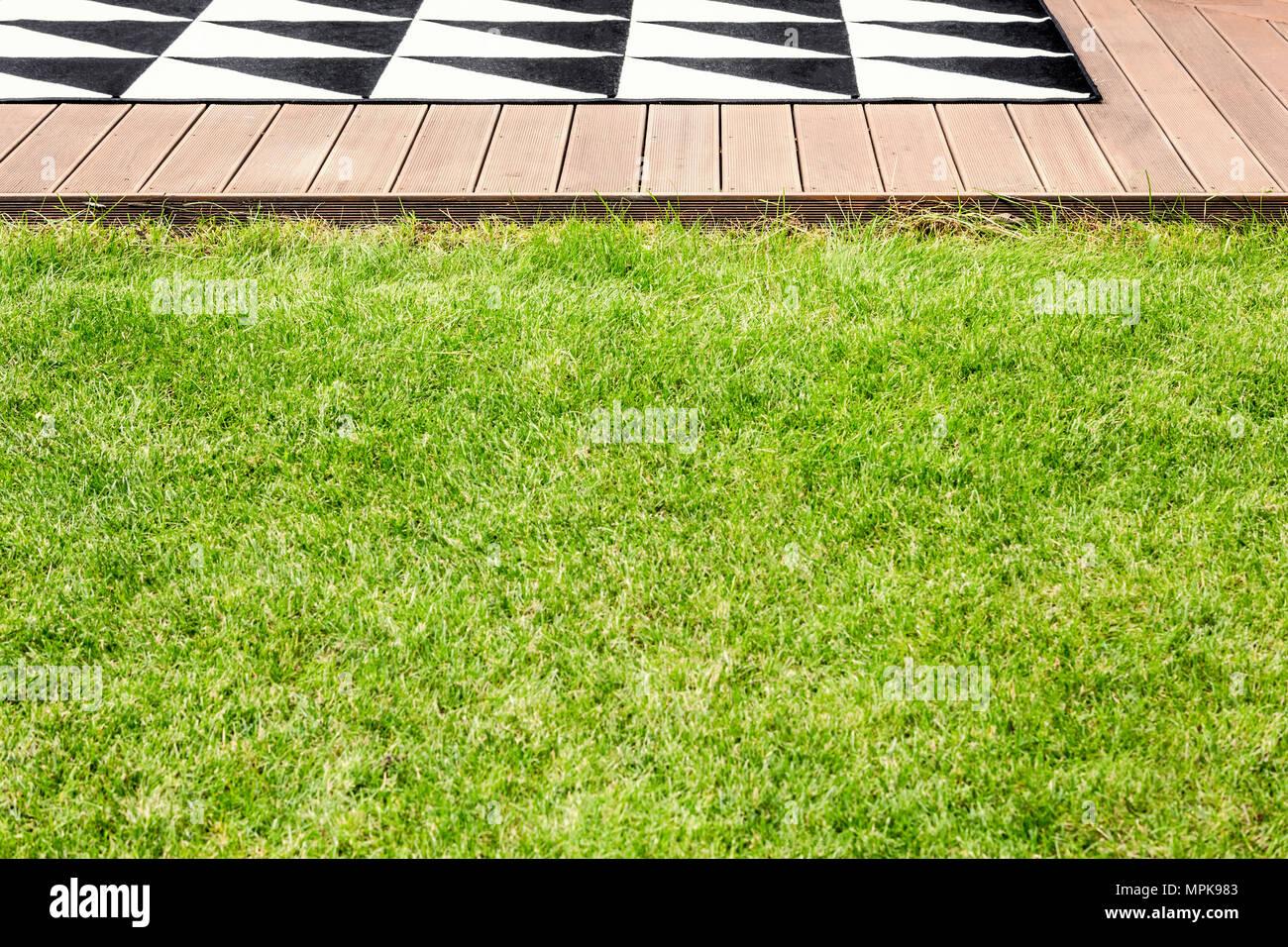 Grünes Gras und eine Holzterrasse mit geometrischen Wolldecke in einem Garten Stockfoto