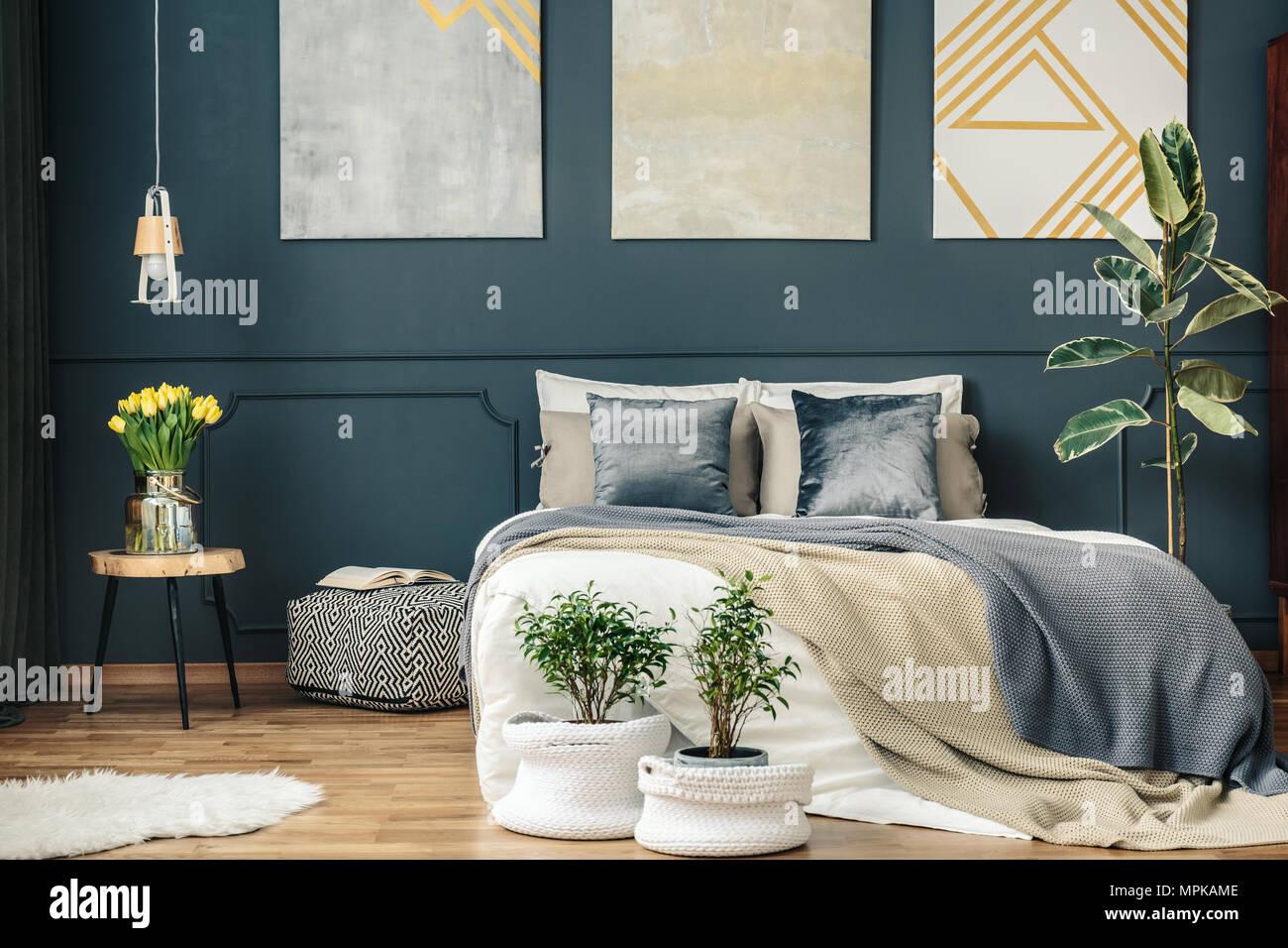 Großes, Gemütliches Bett Unter Poster Auf Dunklen Wand Mit Spritzguss  Und  Unter Pflanzen Im Schlafzimmer Innenraum
