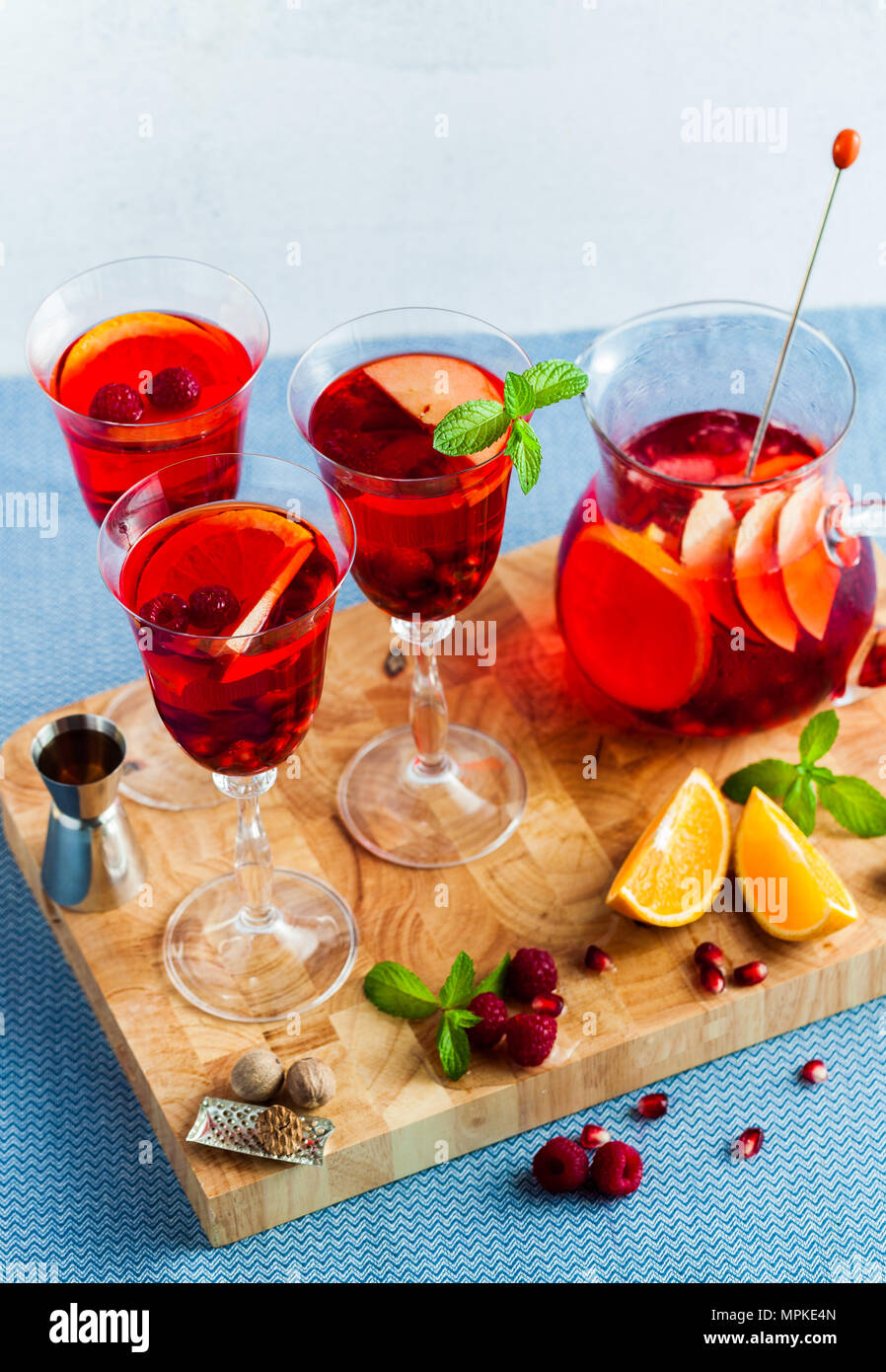 Frische Sommer rote Sangria aus reifen Früchten und Beeren sowie Wein auf dem Tisch in Gläsern und einer Karaffe. Gewürzen und Minze Stockfoto