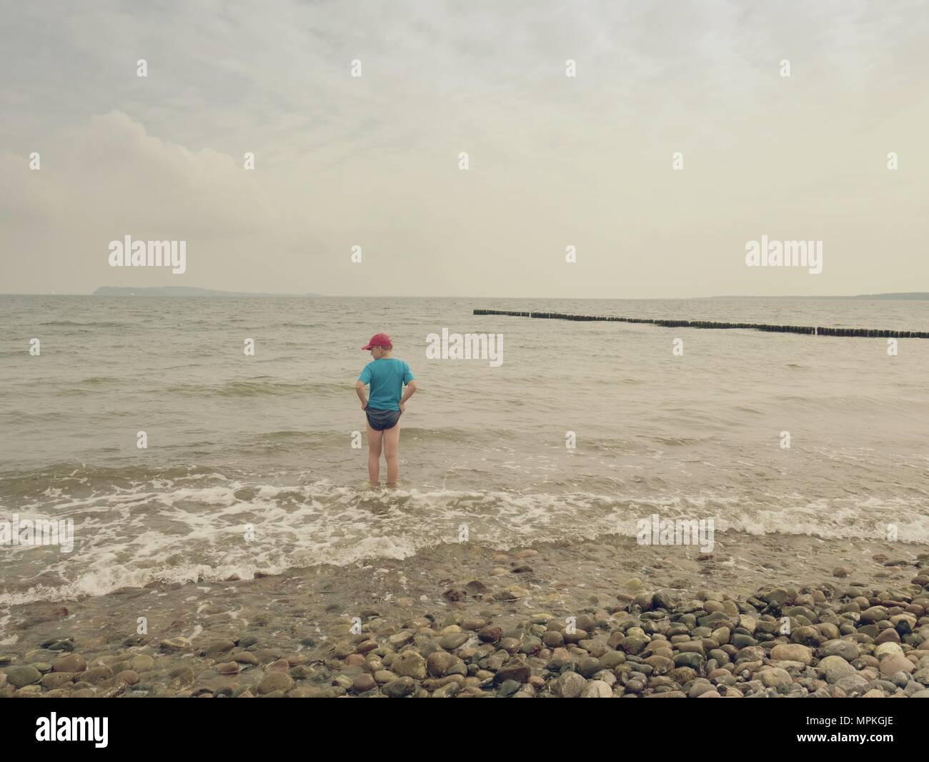 Junge in Blau Schwarz sportliche Kleidung Aufenthalt in kalten schäumende Meer. Blonde Haare Kind in Wellen am steinigen Strand. Windigen Tag, bewölkt blauer Himmel auf Marine Stockbild