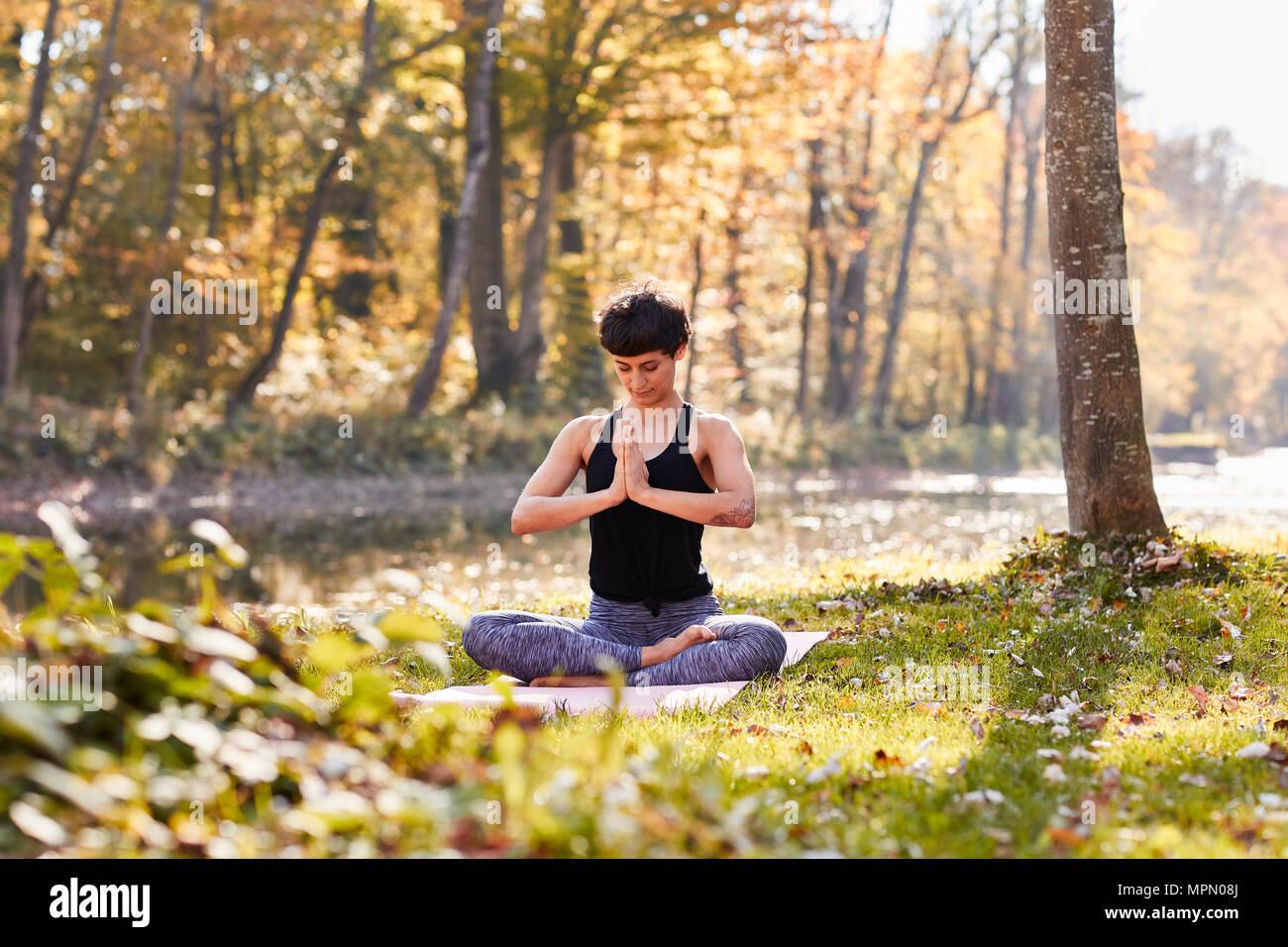 Mitte der erwachsenen Frau im Wald Üben Yoga, Meditation Stockbild