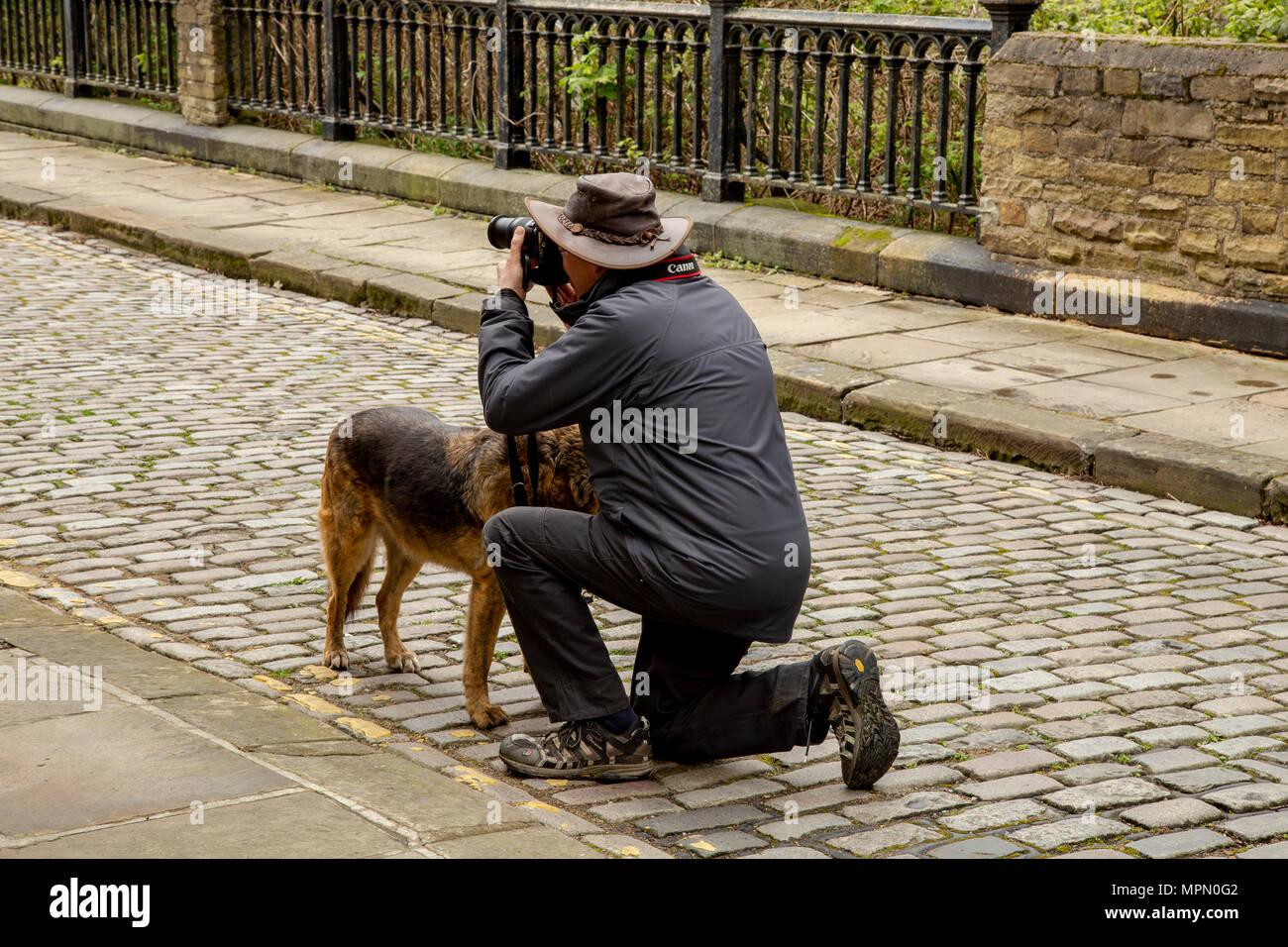 Ein Mann kniet auf einem Foto in Saltair, Yorkshire. Sein Hund steht neben ihm. Stockbild