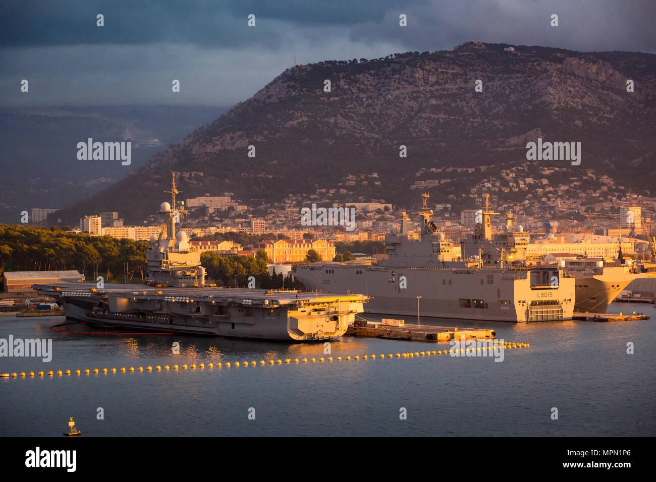 Sonnenaufgang über Atomgetriebenen Flugzeugträger Charles de Gaulle, Tonnerre Hubschrauber und Schiffe der französischen Marine in Toulon, Côte d'Azur, Frankreich Stockbild