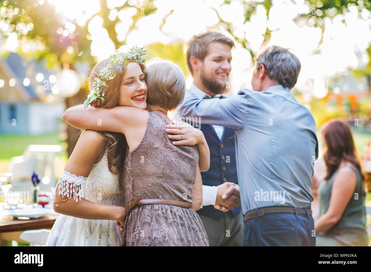 Gäste gratulieren Braut und Bräutigam bei der Hochzeit Empfang draußen im Hinterhof. Stockbild