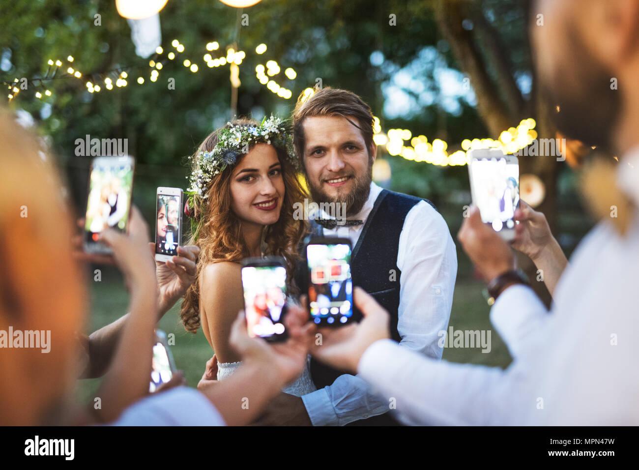 Gäste mit Smartphones unter Foto von Braut und Bräutigam bei der Hochzeit außerhalb. Stockbild
