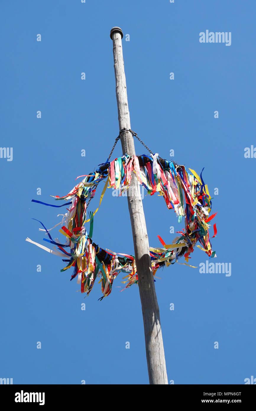 Traditionelle deutsche Maibaum vor blauem Himmel, Mai Feier in Deutschland Stockbild