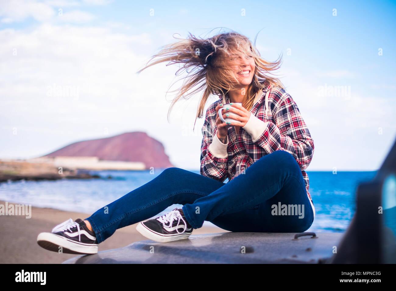 Freiheit und Ferienhäuser Konzept für schöne Blondine kaukasischen junge Frau sitzen auf der Nase von einem off road Black Car. Hintergrundbeleuchtung und Sonnenlicht in wa Stockbild