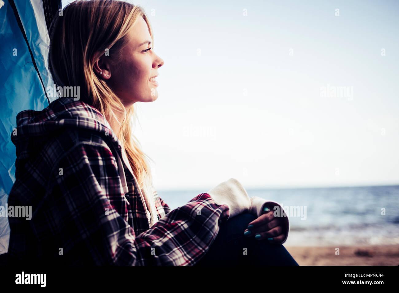 Wanderlust für junge hübsche blonde Frau kaukasischen am Meer, Lächeln, sitzen Sie ihr Zelt am Strand platziert. Ozean und Meer im Hintergrund Stockbild