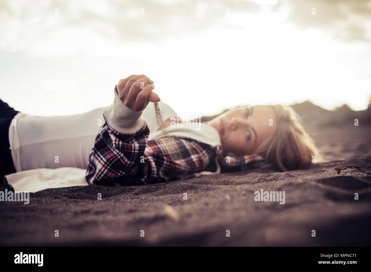 Nette junge Frau am Strand mit Sand fallen von ihrer Hand. Freiheit und Fernweh Konzept im Urlaub Stockbild