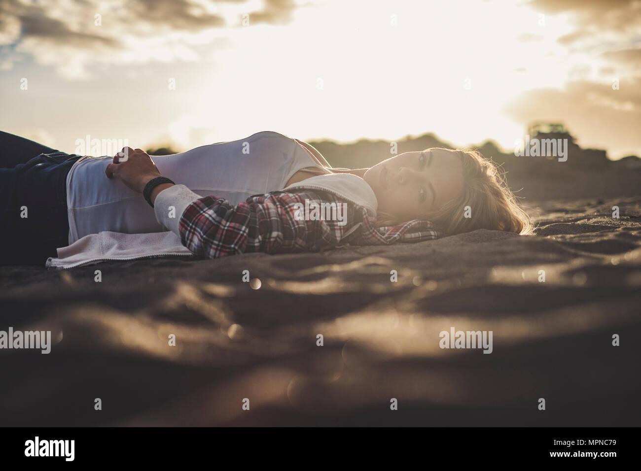 Schönen Sonnenuntergang Licht für eine niedliche blonde Mädchen legt die Ruhe am Strand auf Teneriffa. Sie schauen auf sie. Off road Auto auf dem Hintergrund geparkt Stockbild