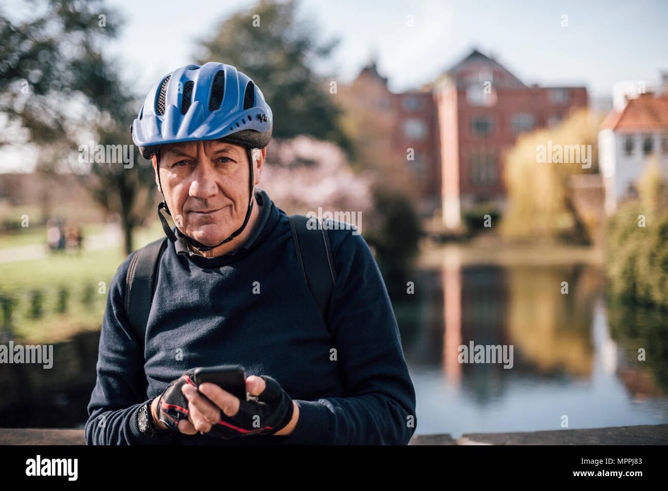 Portrait von älteren Mann mit Radfahren mit Smartphone Helm Stockbild