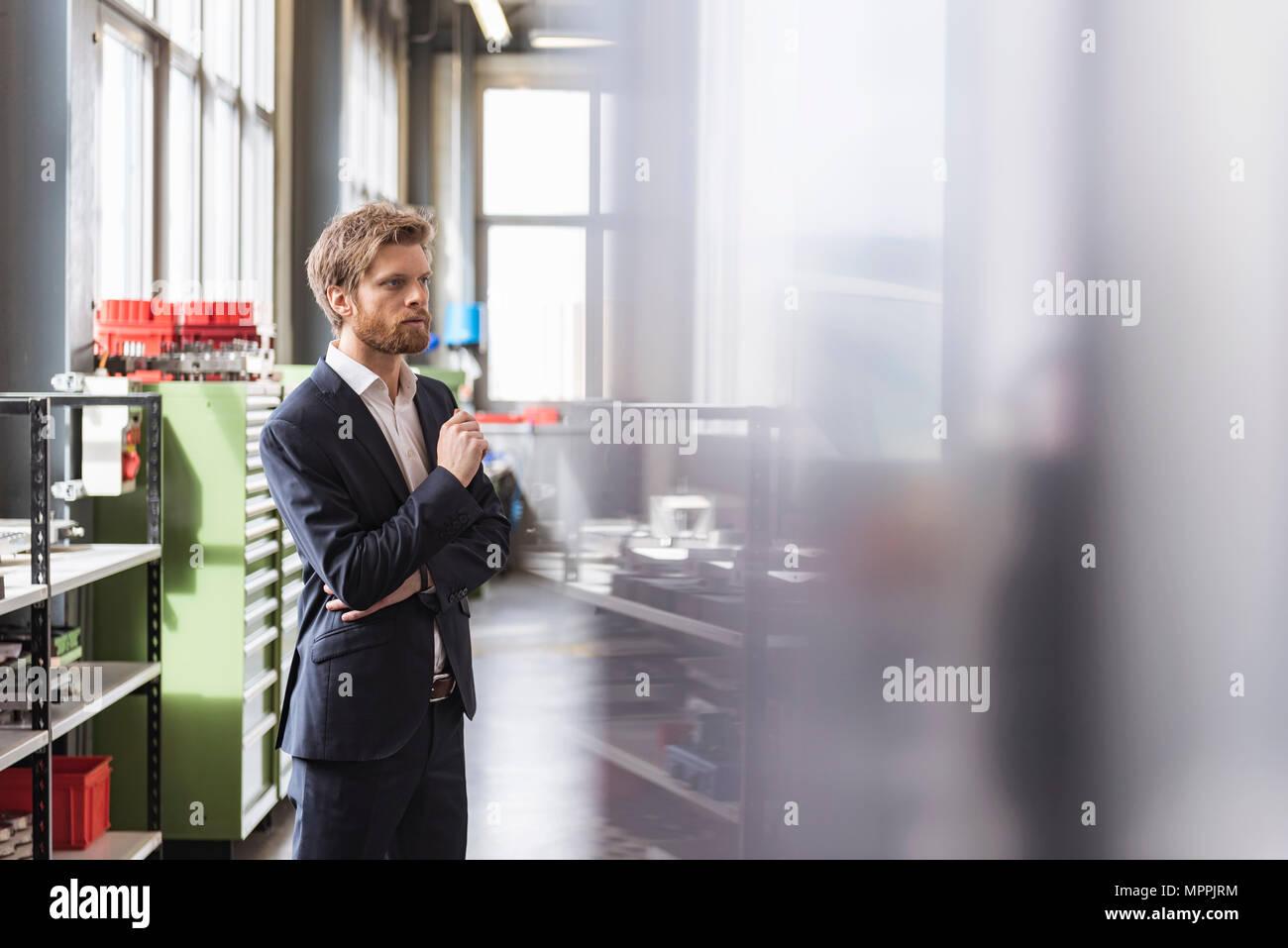 Geschäftsmann in der modernen Fabrik starrte Stockbild