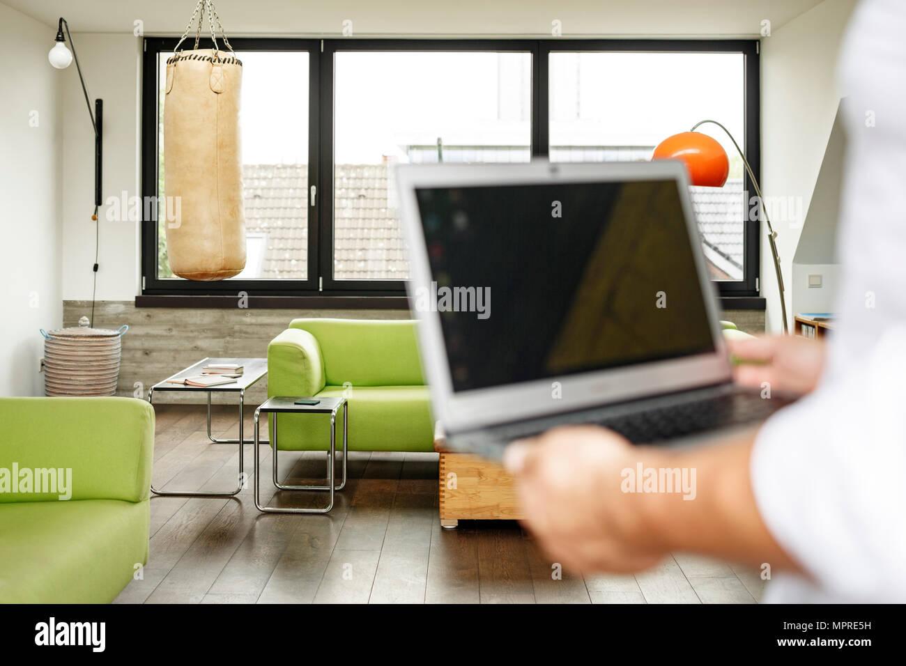 Geschäftsmann, Laptop, Boxsack im Hintergrund Stockfoto