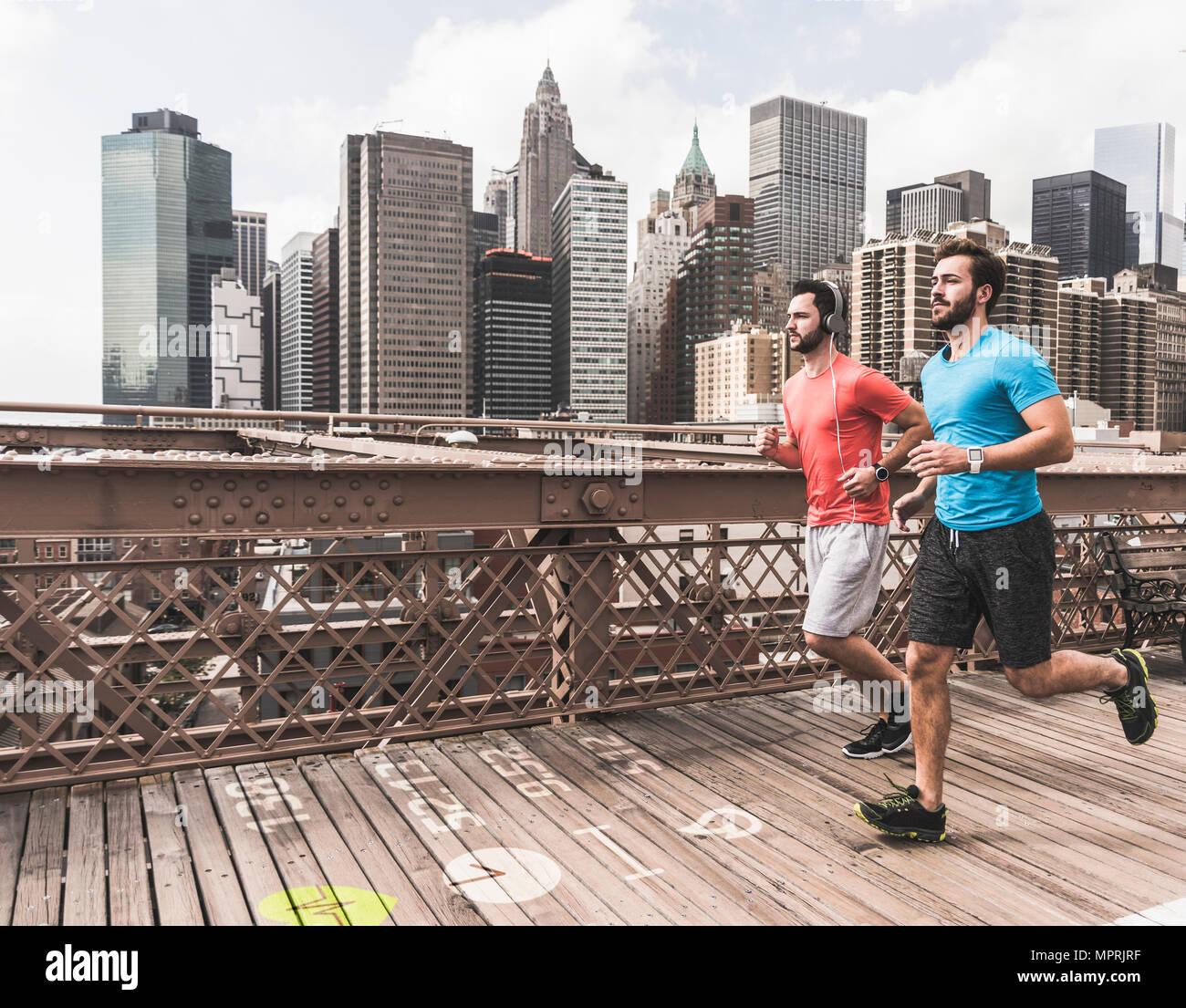 USA, New York City, zwei Männer, die auf Brooklyn Brige mit Daten, die auf dem Boden Stockbild