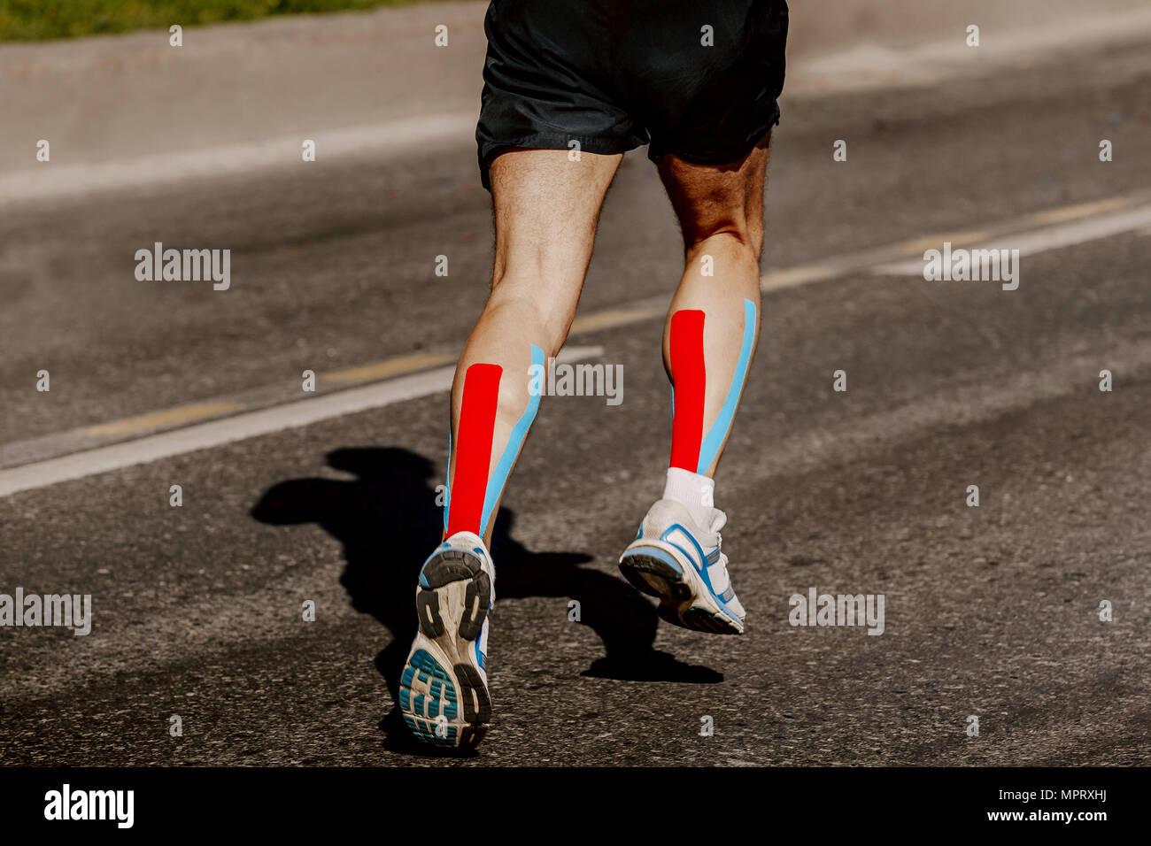 Beine Läufer mit kinesio Tape auf wadenmuskel Betrieb Straße ...