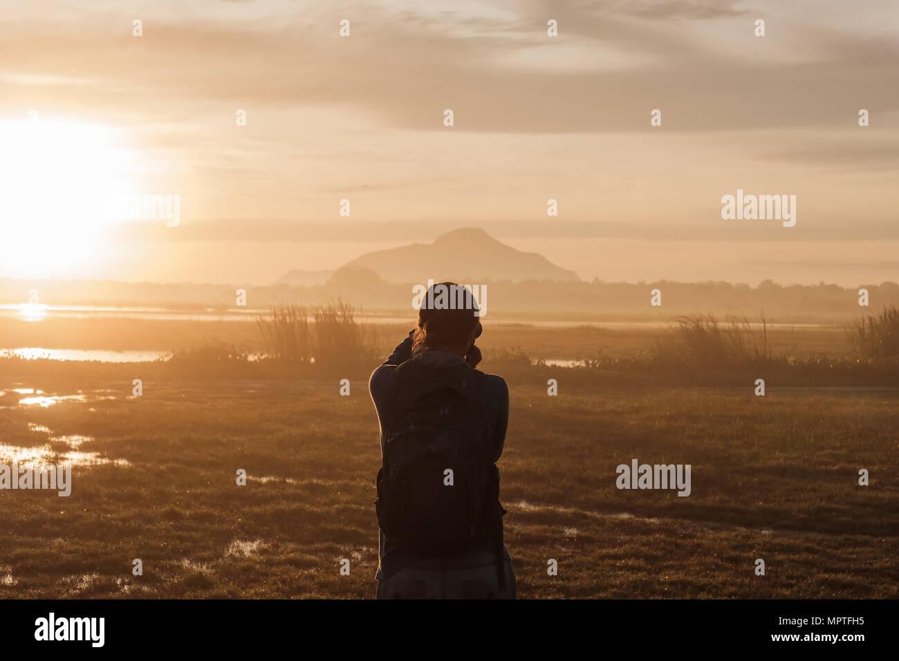 Silhouette einer Frau mit einem Smartphone Bilder aufnehmen bei Sonnenaufgang oder Sonnenuntergang. Stockfoto