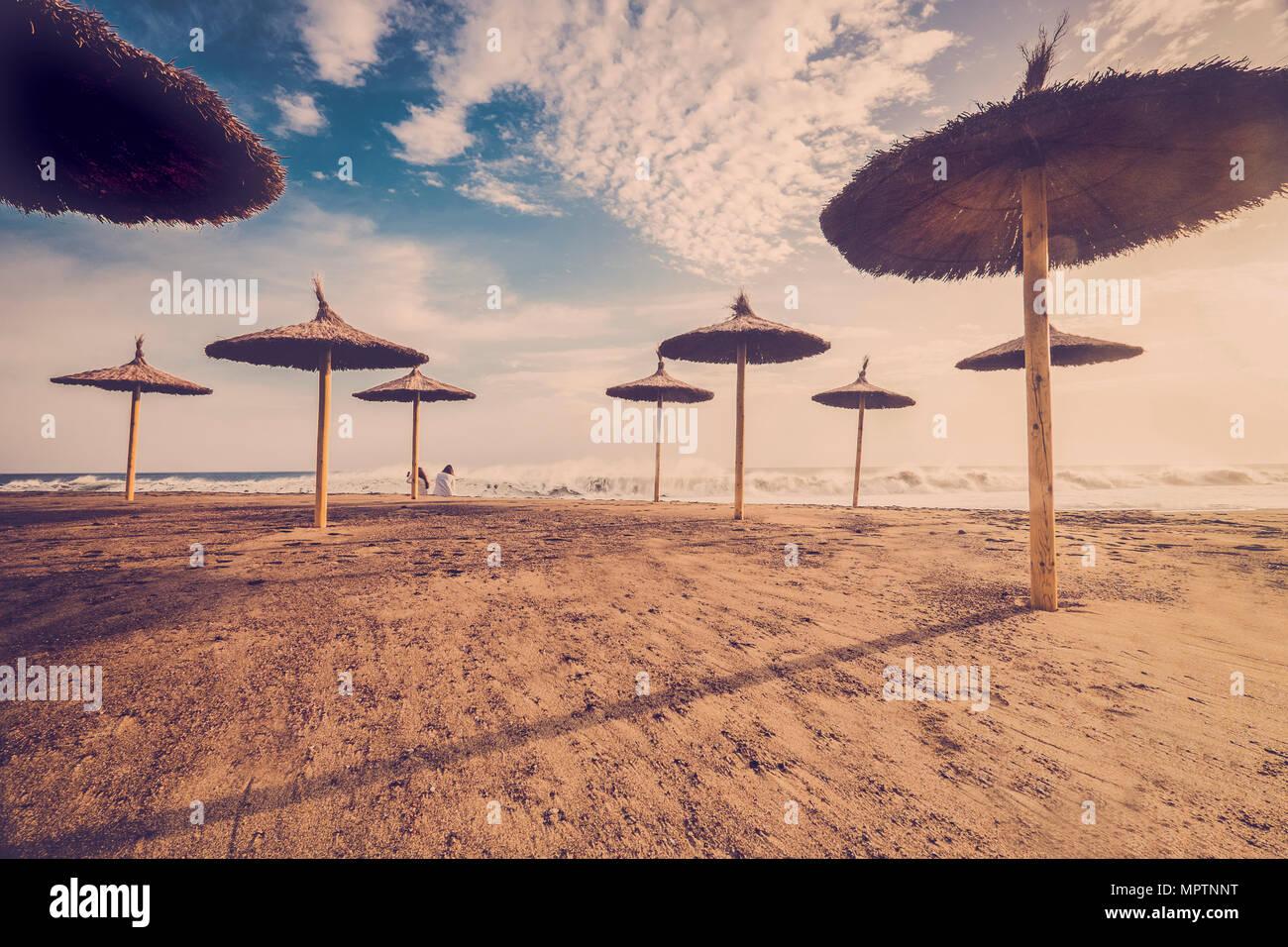 2 Frauen am Strand mit viel Stroh Sonnenschirme bewundern, das Meer und die Wellen an einem schönen Sommertag Stockbild