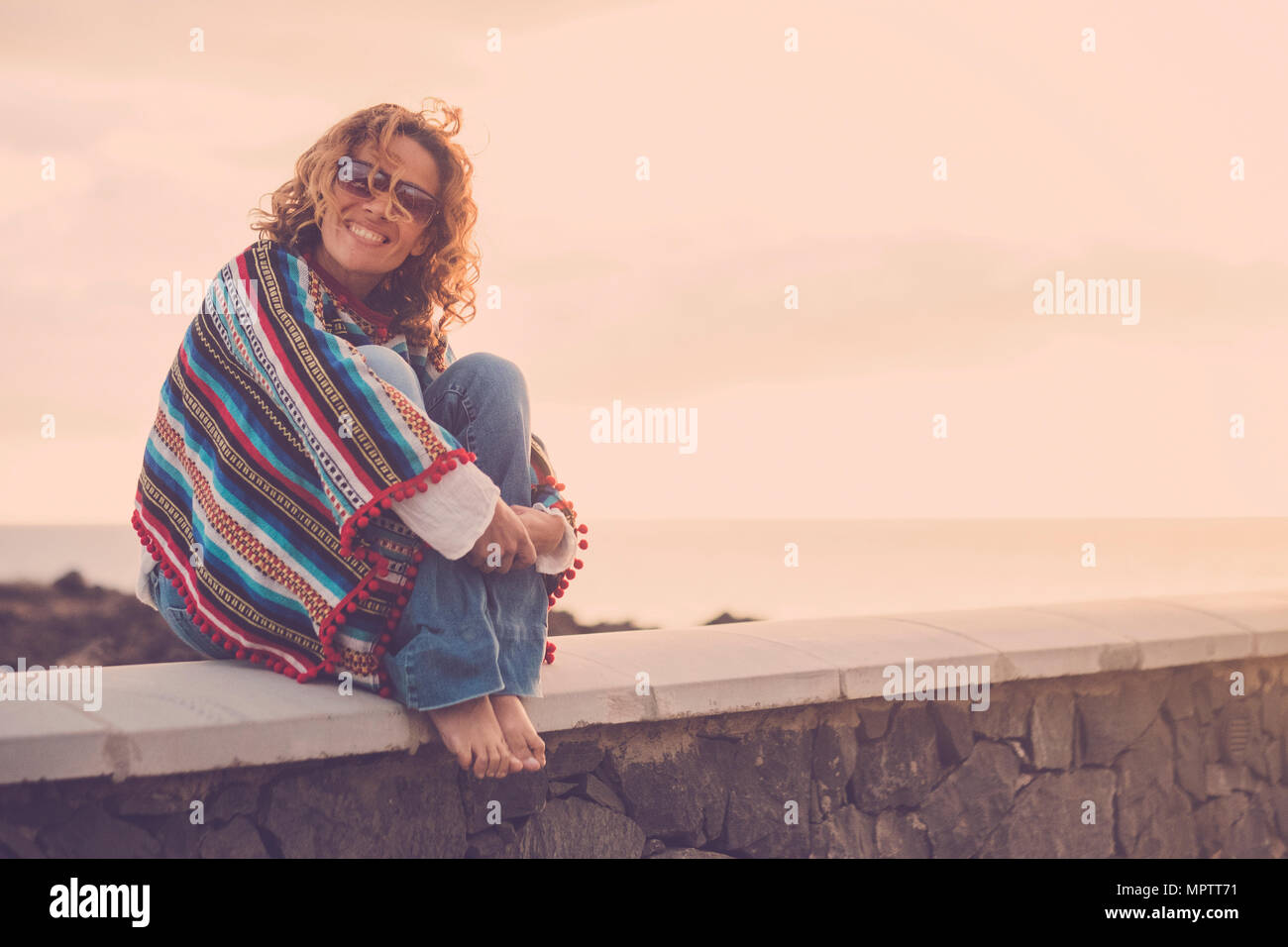 Schöne nette Dame mit Swirl Haar lächelte sie, während Sie in der Nähe des Ozeans sitzen. Poncho und hippy Kleidung Freiheit Konzept darzustellen. Ferienhäuser sty Stockbild