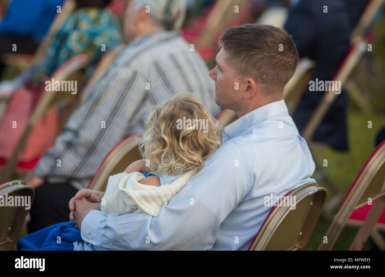 Ein Vater hält seine Tochter während der Predigt während der jährlichen Easter Sunrise Zeremonie, Camp Lejeune, N.C., 16. April 2017 hören. Jedes Jahr das Marine Corps Installationen Osten Kaplan hosts Die Easter Sunrise Zeremonie für die Marines und Seeleute, ihre Familien zu bringen und das Osterfest feiern. (U.S. Marine Corps Foto von Lance Cpl. Ashley D. Gomez) Stockbild
