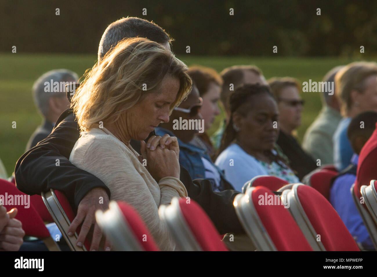 Eine Frau beugt den Kopf im Gebet während der jährlichen Easter Sunrise Zeremonie, Camp Lejeune, N.C., 16. April 2017. Jedes Jahr das Marine Corps Installationen Osten Kaplan hosts Die Easter Sunrise Zeremonie für die Marines und Seeleute, ihre Familien zu bringen und das Osterfest feiern. (U.S. Marine Corps Foto von Lance Cpl. Ashley D. Gomez) Stockbild