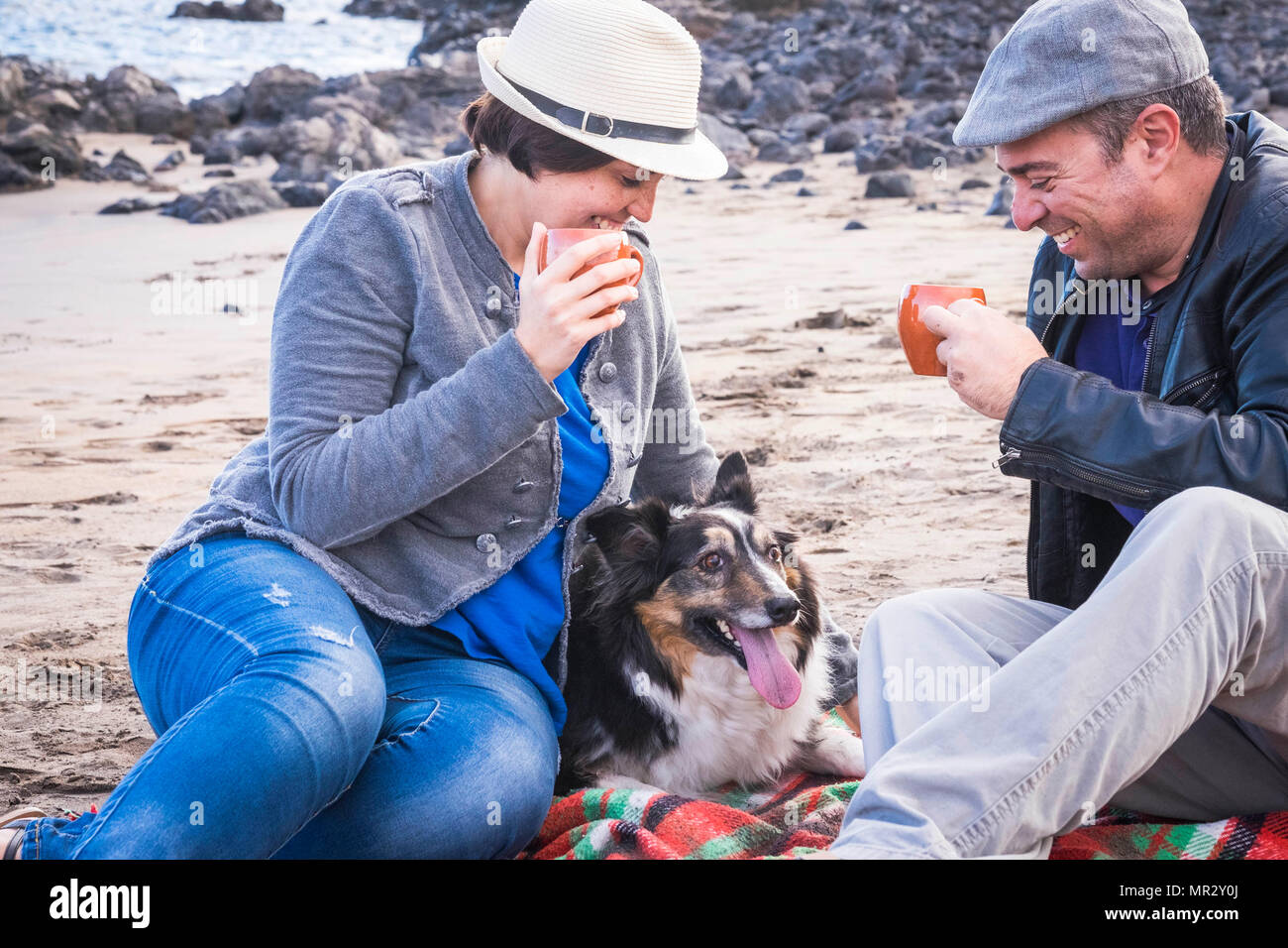 Schöne Paar mittleren Alters in der Freizeit am Strand im Urlaub im Sommer mit einem süßen Haustier Border Collie. Alle zusammen mit einer Tasse Kaffee zu anejoy Stockbild