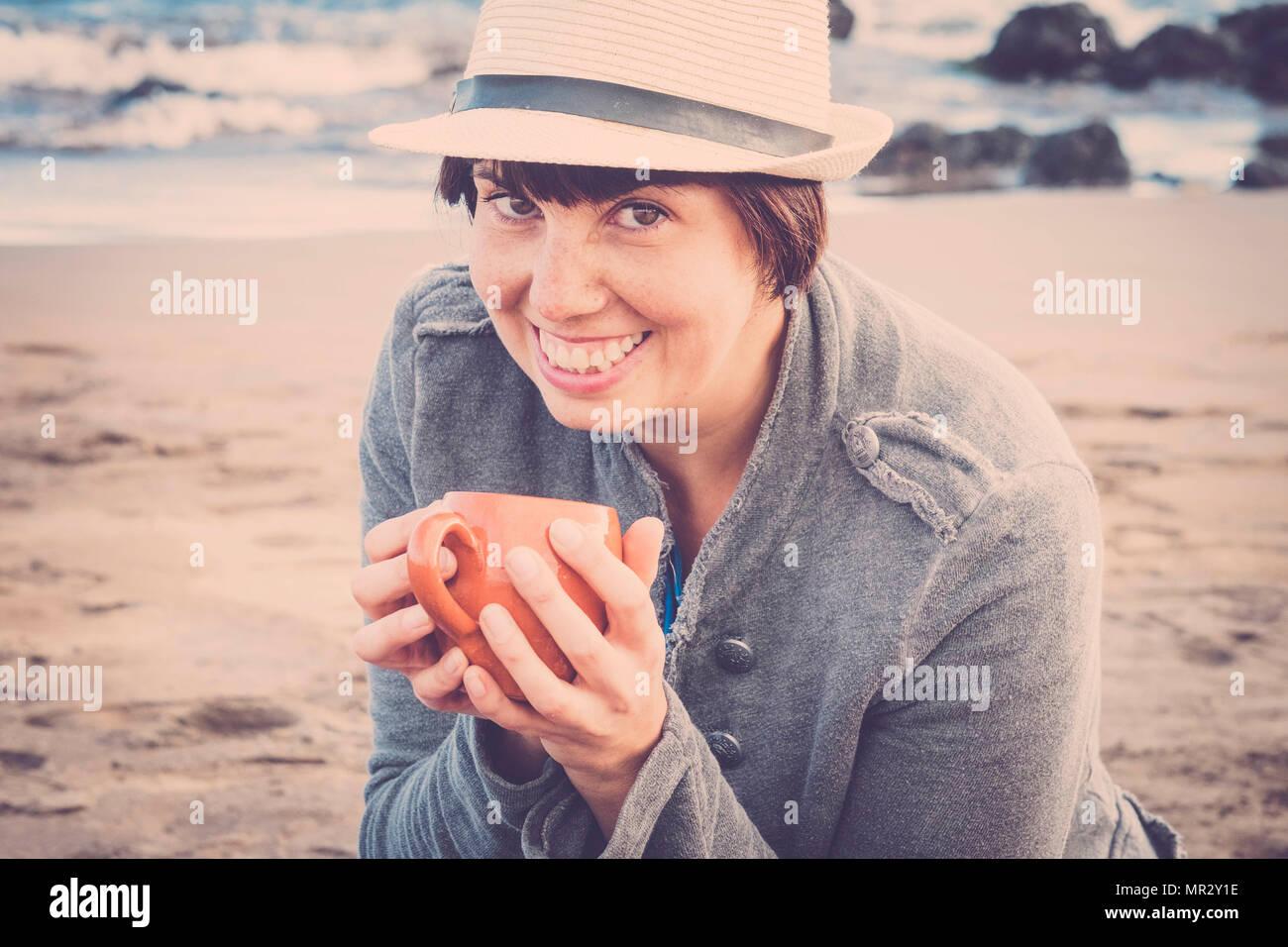 Nett lächelnden jungen Frau sitzen unten am Strand mit Blick auf das Meer im Hintergrund. trinken eine Tasse Tee oder Kaffee für eine Freizeitaktivität relalxed und angeschlossen Stockbild
