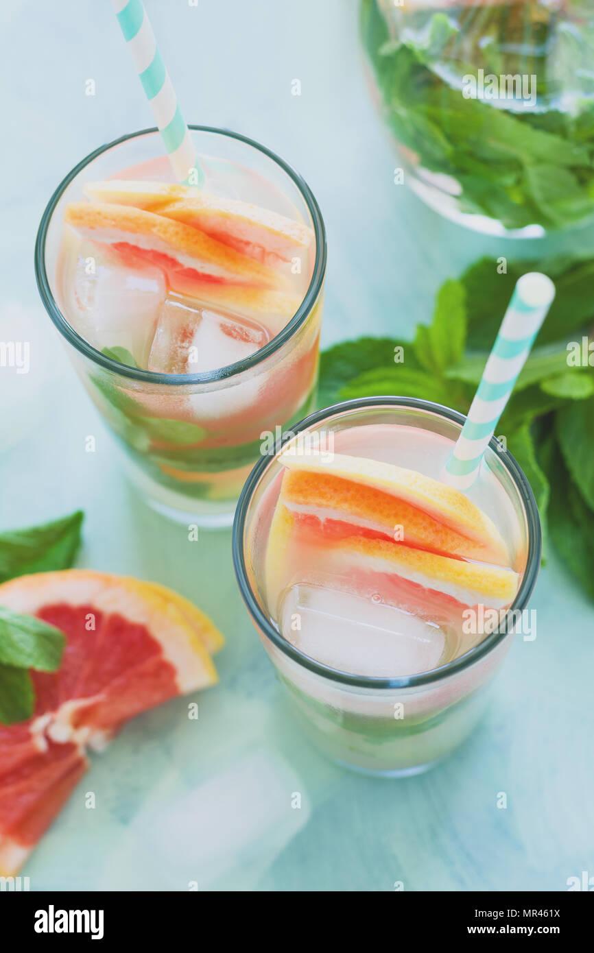 Erfrischung grapefruit Cocktail mit Minze auf mint Farbe Hintergrund. Gesund Zitrusfrüchte im Sommer trinken. Getönt Stockbild