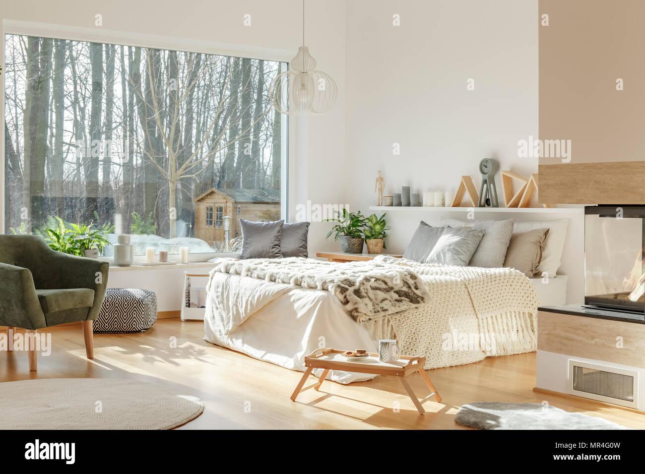 Grau Sessel neben einem weißen Bett mit Fell im Schlafzimmer ...
