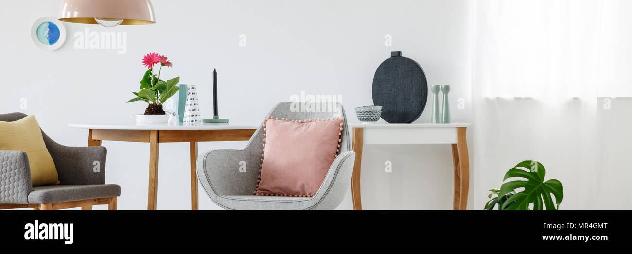 Puder Pink Kissens auf einem grauen Sessel neben einem Tisch mit ...