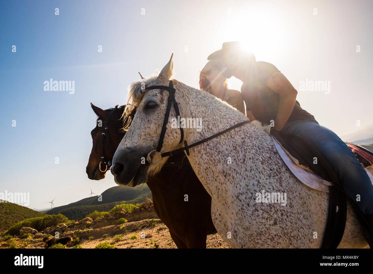 Liebe Szene zwischen junge Schöne coule reiten zwei nette Pferde in der Natur. Windmühle für grüne Energie und bessere Zukunft im Hintergrund. Alternativ Stockbild
