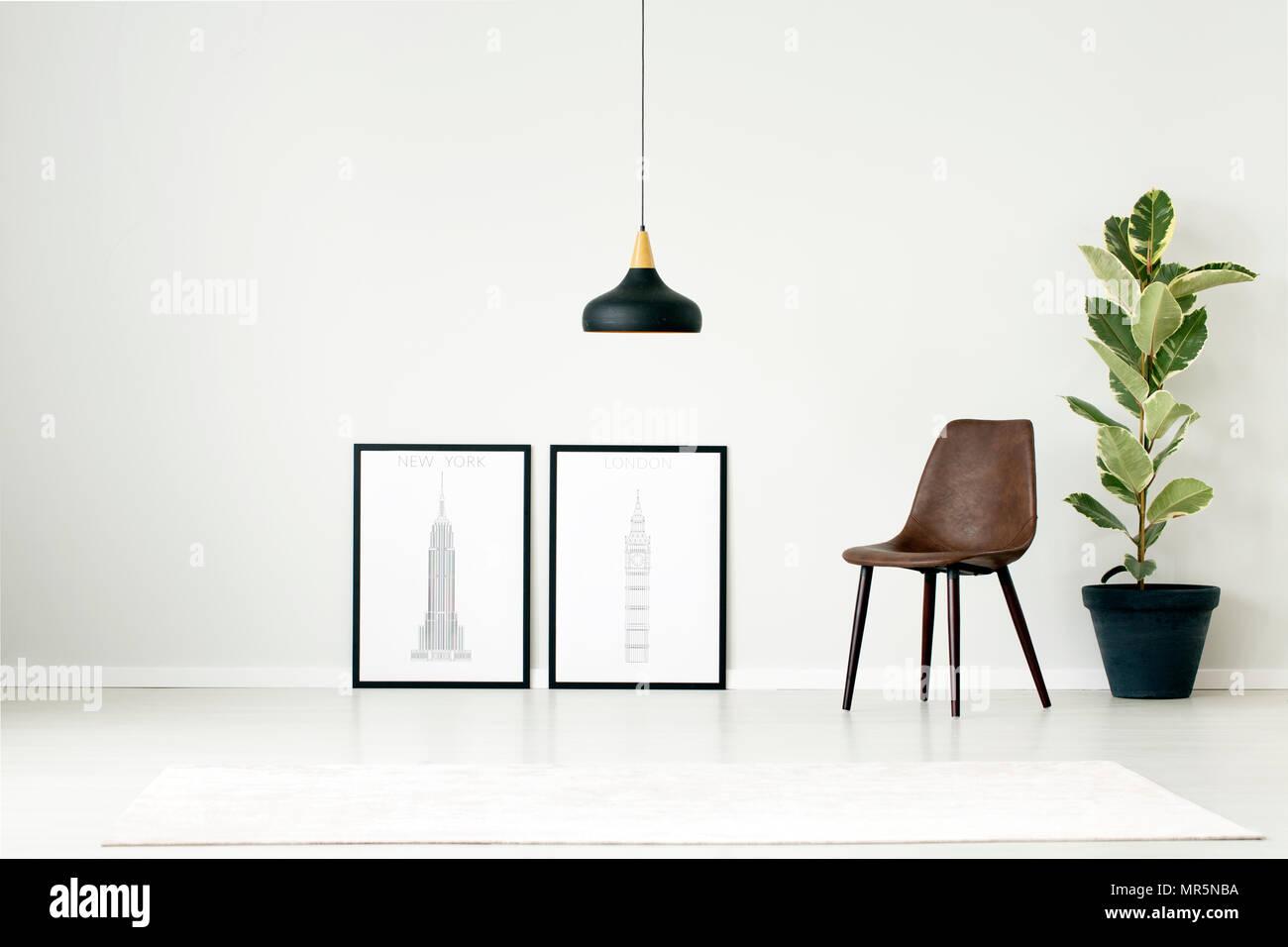 Braun Stuhl zwischen Plakate und Pflanze gegen weiße Wand mit Kopie ...