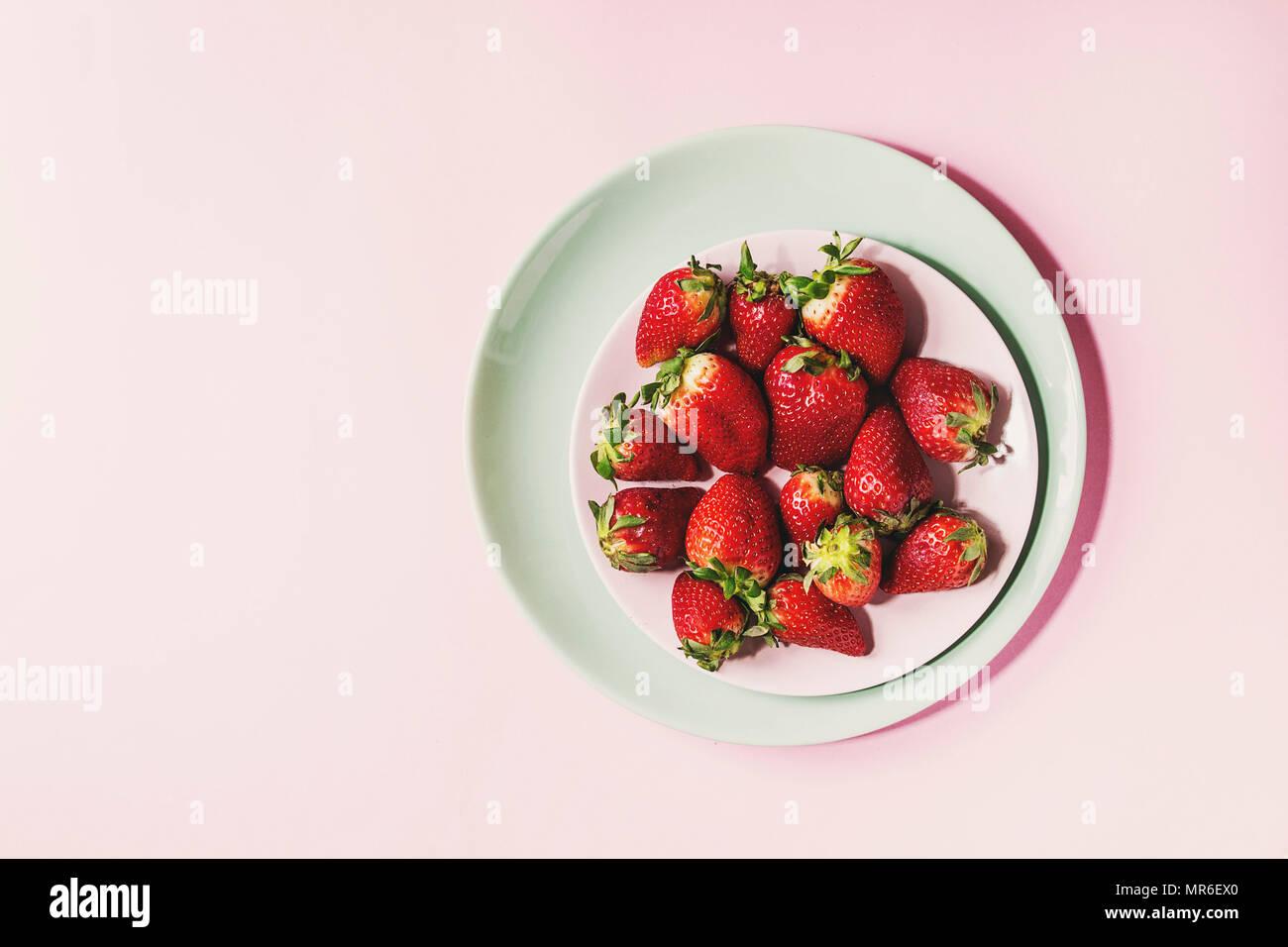 Frische Erdbeeren auf Türkis Platte über Rosa pastell Pin-up-Hintergrund. Kopieren Sie Platz. Ansicht von oben Stockbild