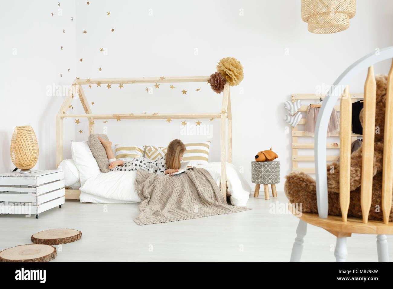 Mädchen lesen Sie ein Buch auf Ihrem Bett in Weiß und Beige ...