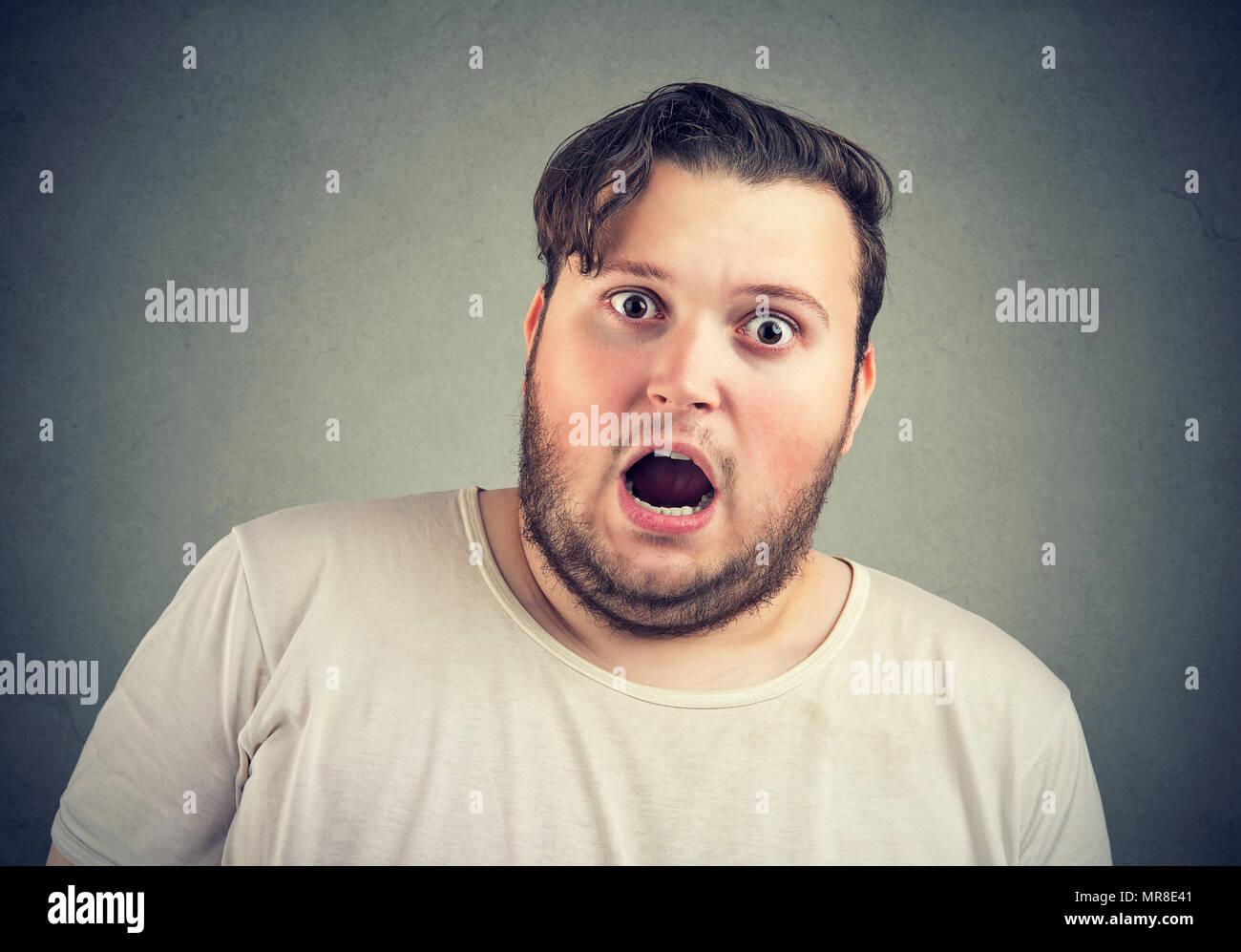 Nahaufnahme der übergewichtigen Mann, Angst mit dem Mund an der Kamera auf grauem Hintergrund geöffnet. Stockbild