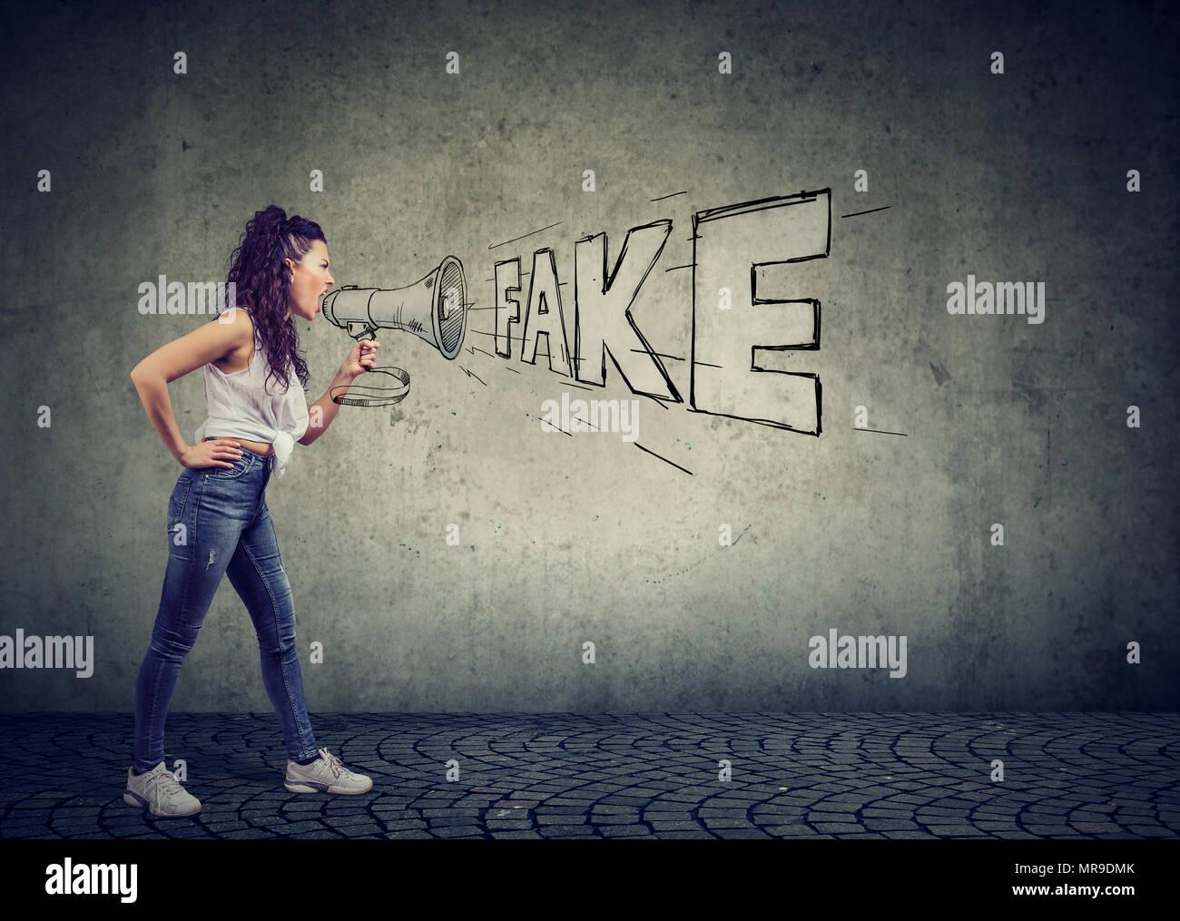 Seitenansicht des Casual Mädchen schreien mit Megafon, gefälschte Nachrichten und Propaganda auf grauem Hintergrund. Stockbild
