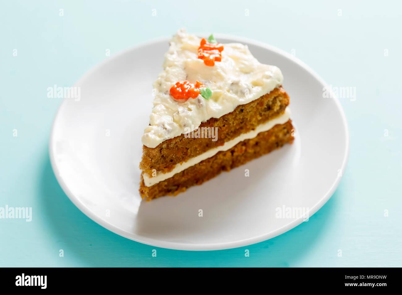 Stück Karottenkuchen mit Zuckerguss und Karotte Dekoration. Stockbild