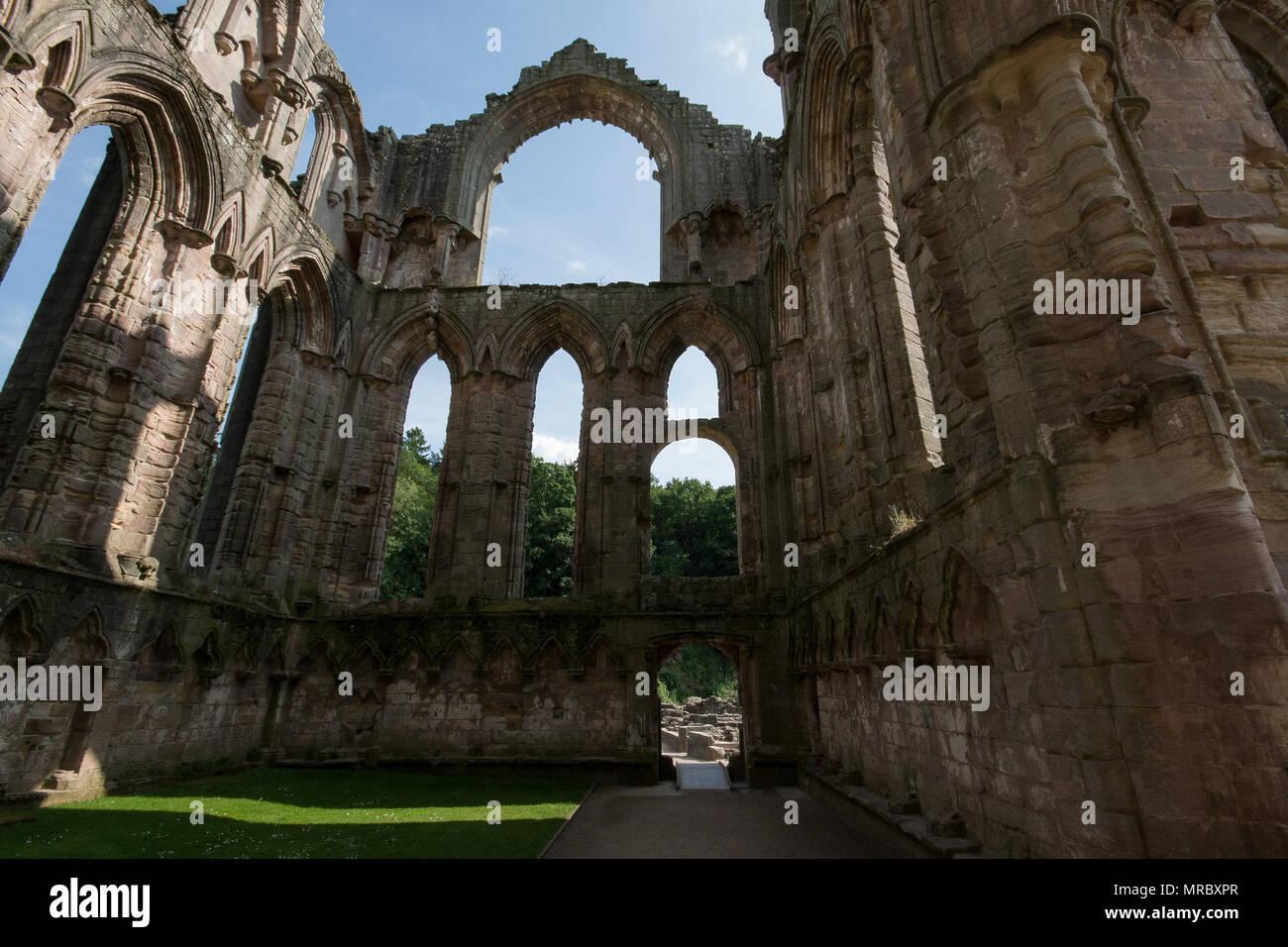 Architektur mit hohen gotischen Bögen im Inneren des Klosters Ruinen von Fountains Abbey, Ripon, Großbritannien Stockbild