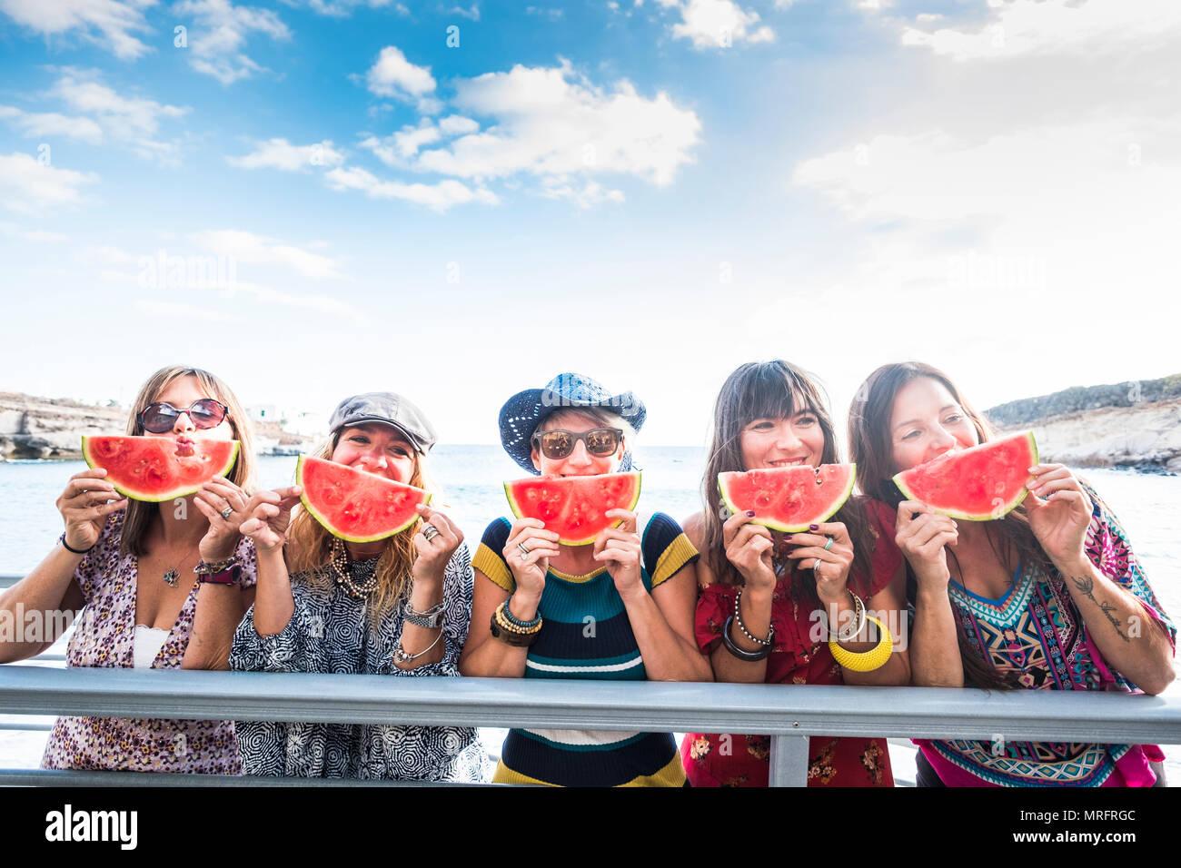 Fünf schöne glückliche junge Frauen kaukasischen Essen Wassermelone Sommer und warmen Tag mit Sonne in der Nähe des Ozeans zu feiern. schöne Farben für die Gruppe Stockbild