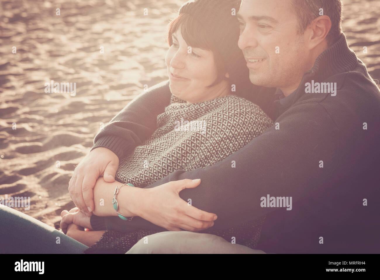 Schöne schöne Mitte Alter 40 Jahre alte Paar Mann und Frau kaukasischen umarmte und zusammen am Strand im sand sitzen bleiben und genießen ein Golde ein Stockbild