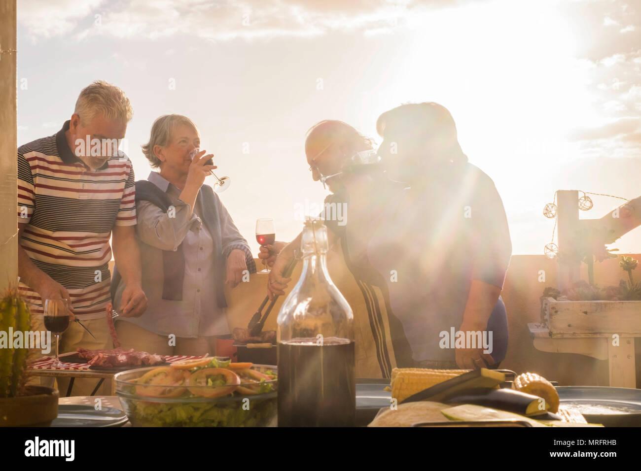 Zwei reift nach paar Kaukasier, Spaß haben das Abendessen im Sonnenuntergang auf der Dachterrasse im Freien zu Hause genießen. goldenen Tönen für leis Stockbild